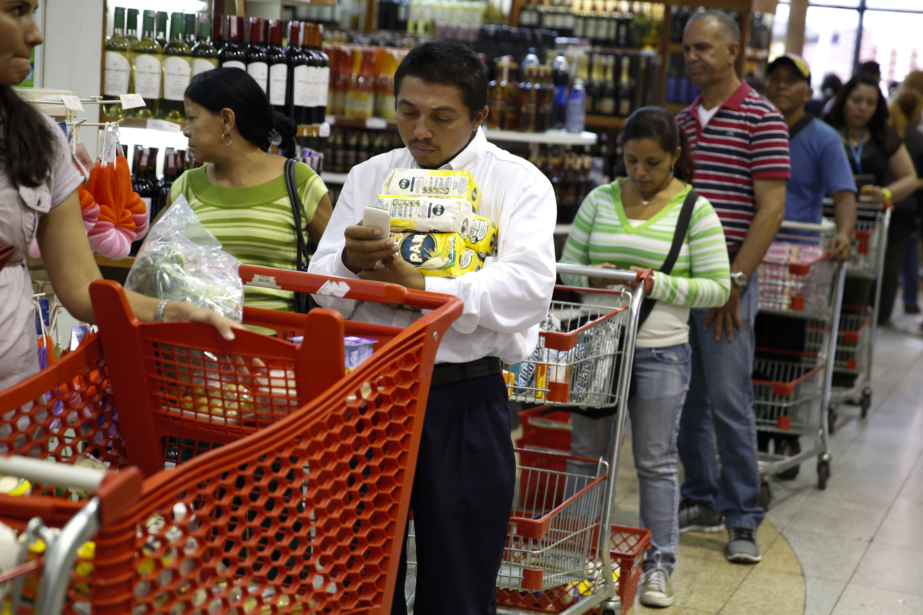 People stand at the checkout line at a supermarket in Caracas on Aug. 21, 2014.