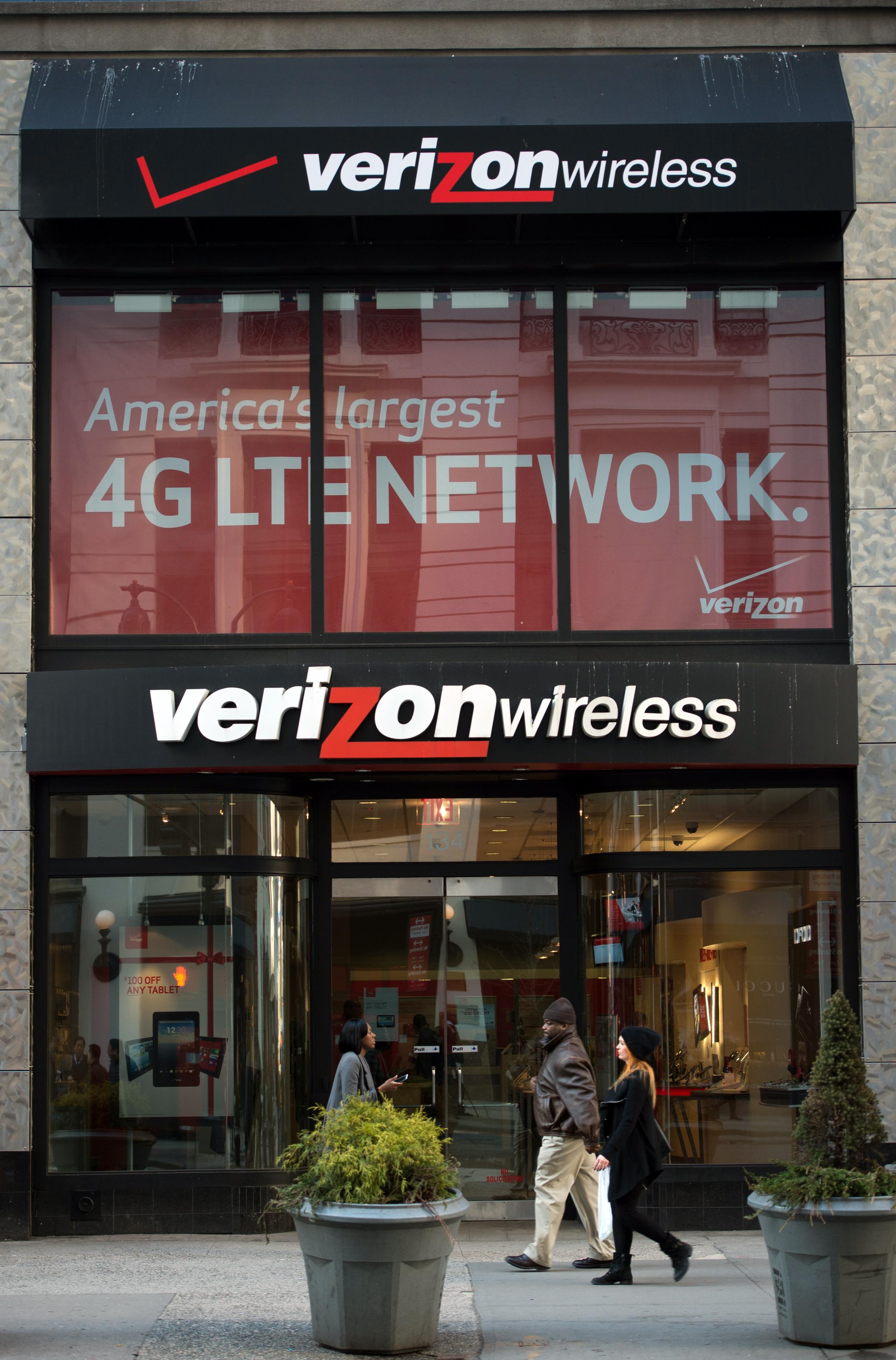 Pedestrians walk past a Verizon Wireless store in New York, U.S., on Friday, Jan. 17, 2014.