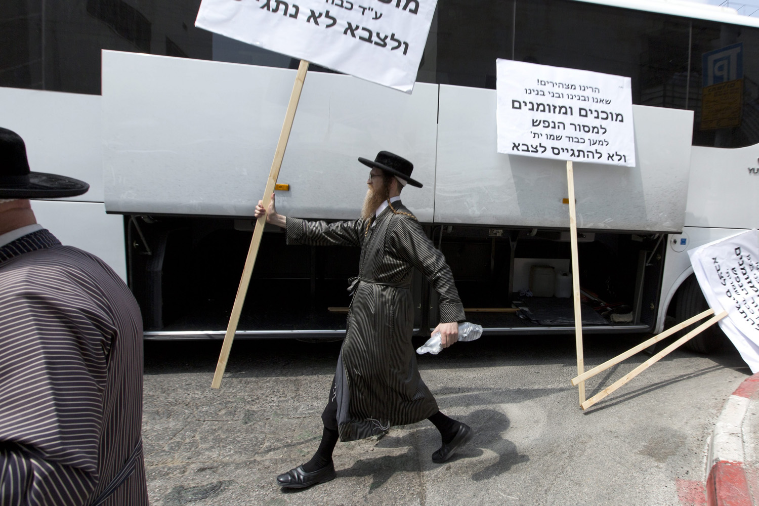 Aug. 31, 2014. An ultra-Orthodox Jew  carries a placard which reads, 'Israeli police. We and our sons are ready to be arrested to honour God, but will not be drafted into the army.'