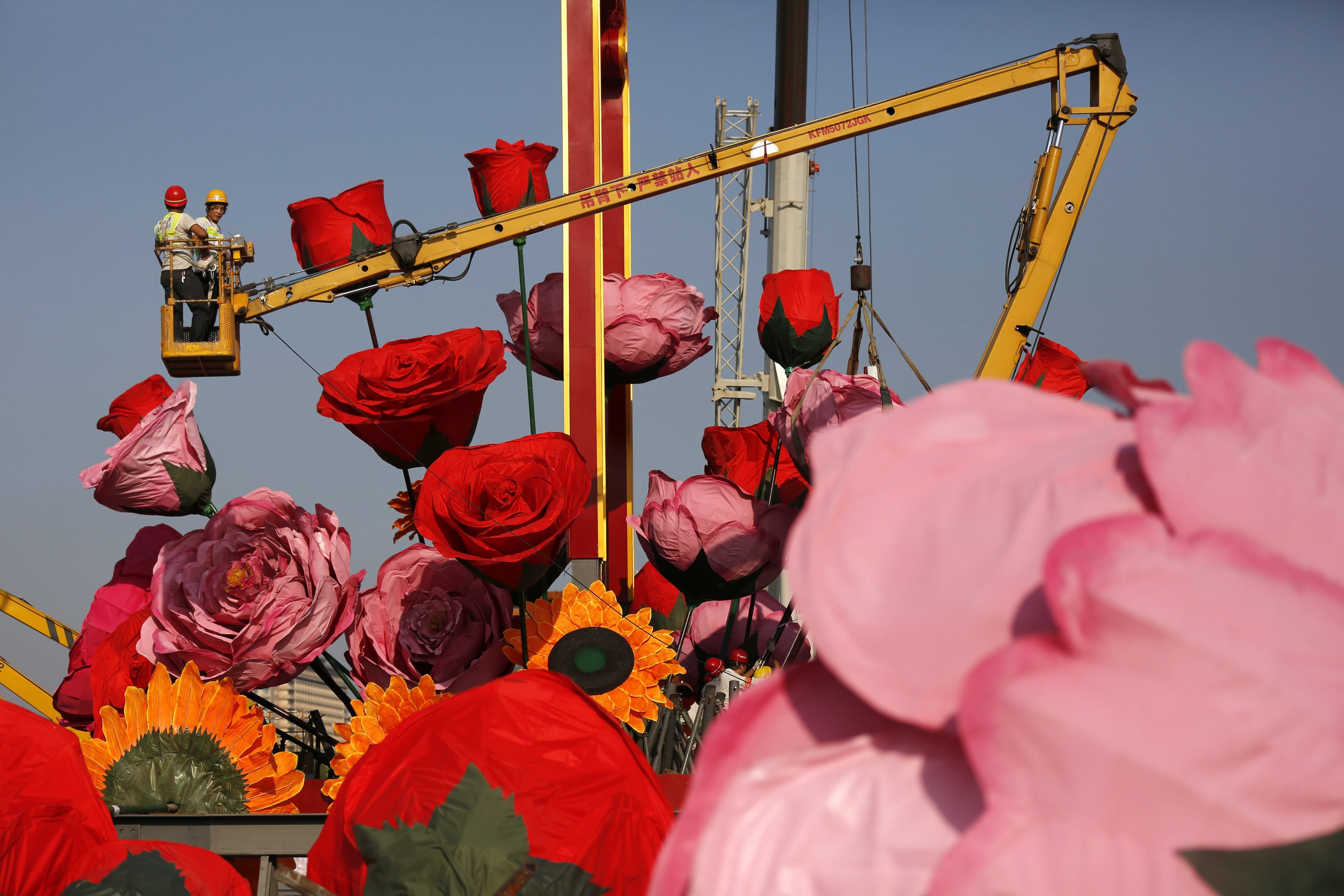 Chinese workers set up giant decoration flowers in preparation for National Day at Tiananmen Square in Beijing on Sept. 18, 2014.