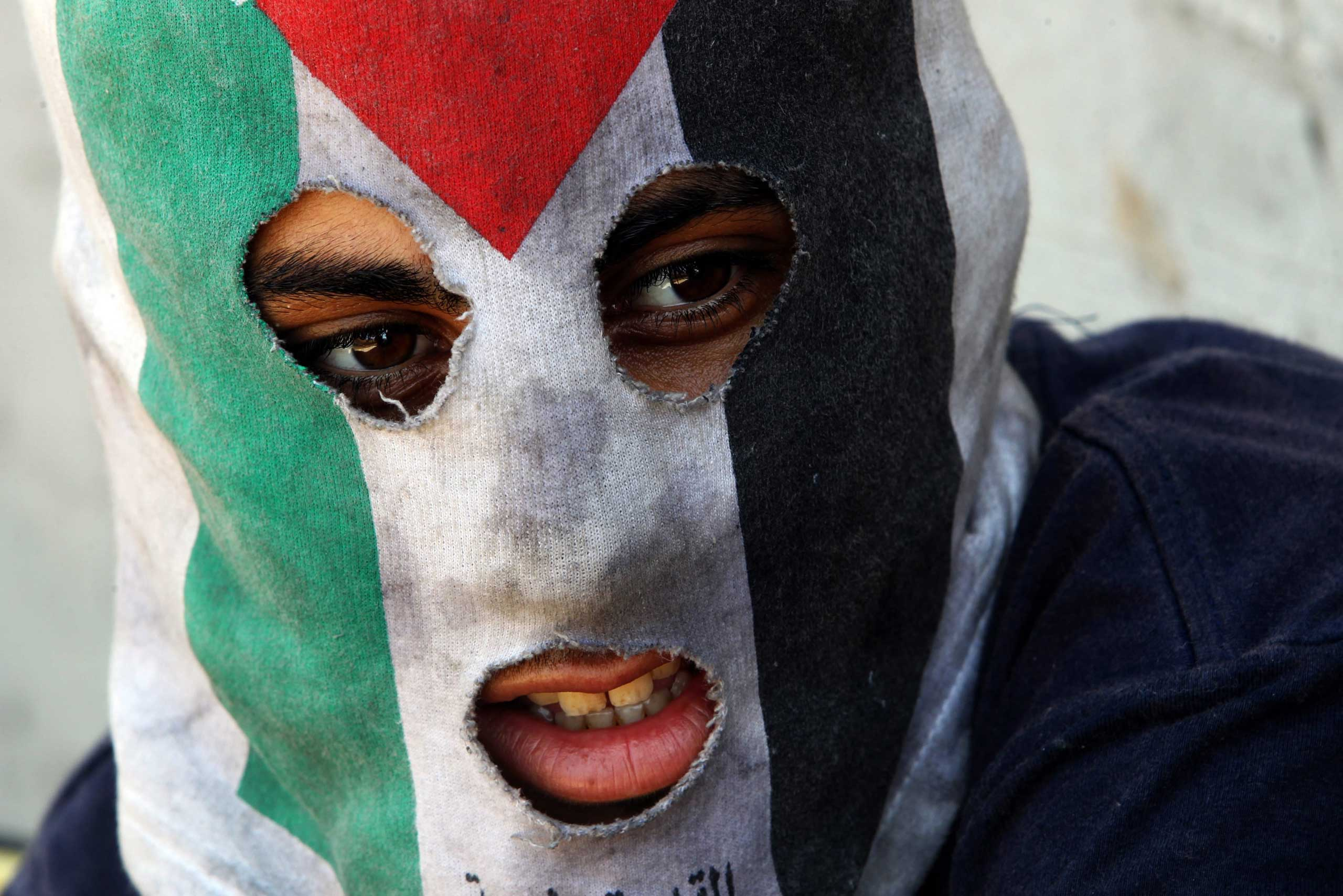 Sept. 19, 2014. A Palestinian protester wears a mask during clashes over the Jewish settlement of Qadomem at Kofr Qadom village, near West Bank city of Nablus.