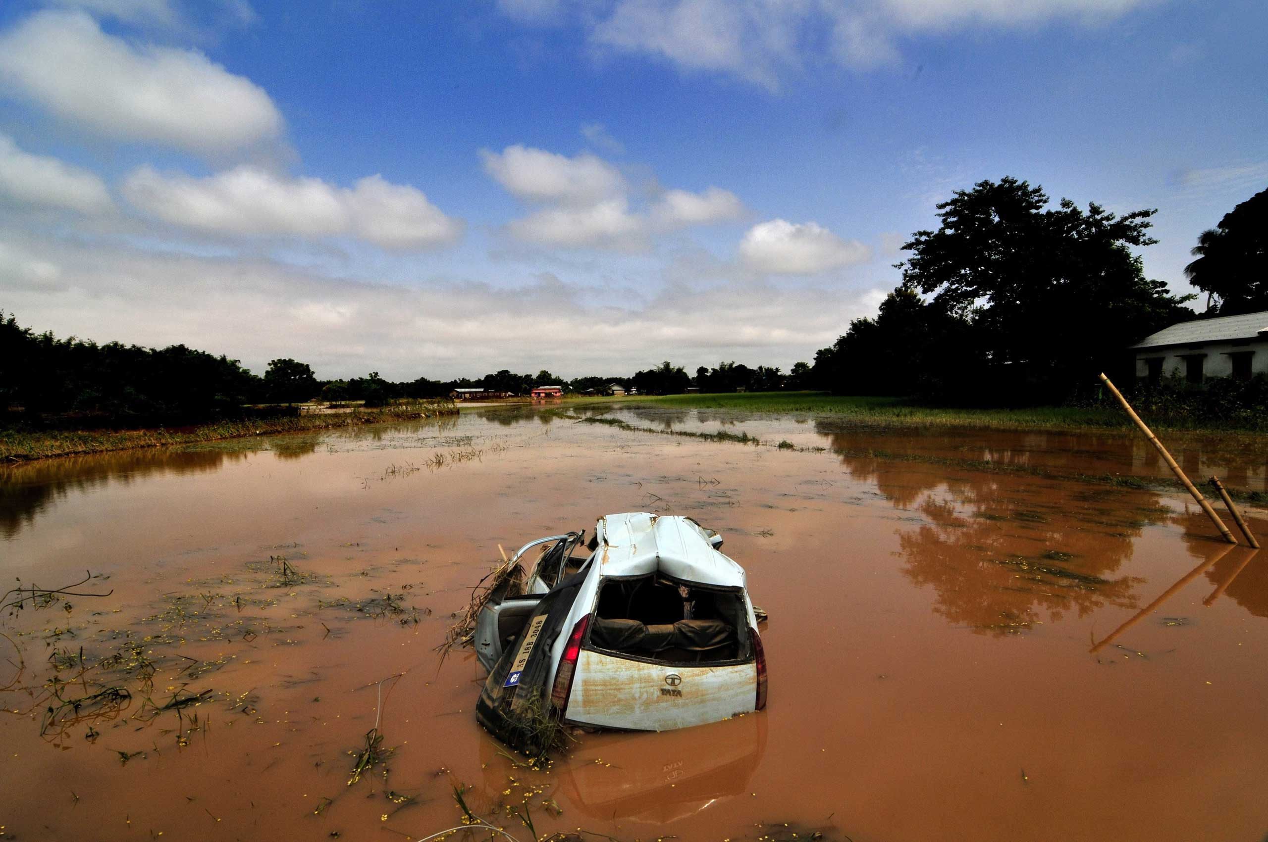 Sept. 24, 2014. A damaged car is surrounded by floodwaters in an agricultural field in Krishnai village, Goalpara district in Assam state, India.