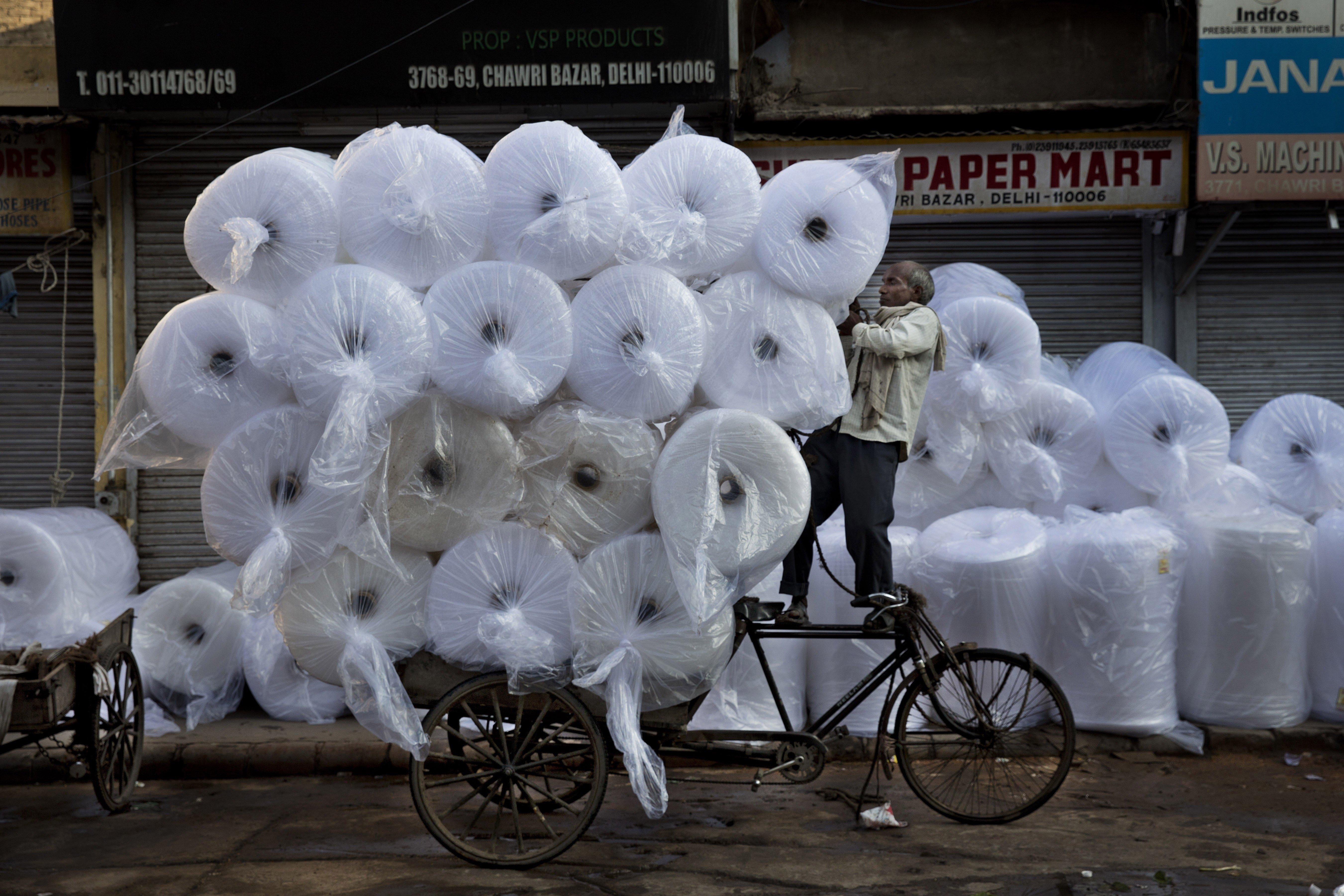 An Indian laborer loads goods on a bike at Chawri Bazar, in New Delhi on Sept. 1, 2014.