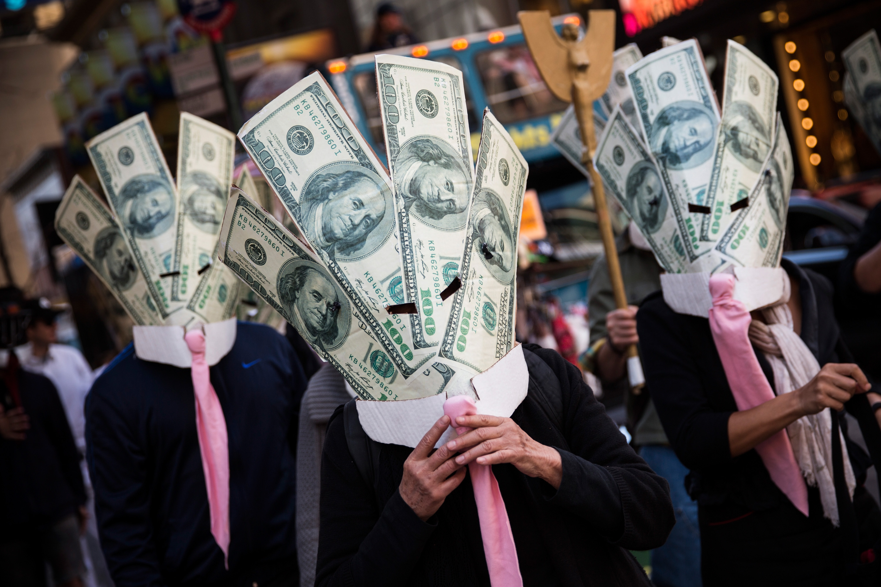 Occupy Wall Street protesters wearing masks made out of enlarged dollar bills act in a short skit in Times Square in New York City on Sept. 17, 2013