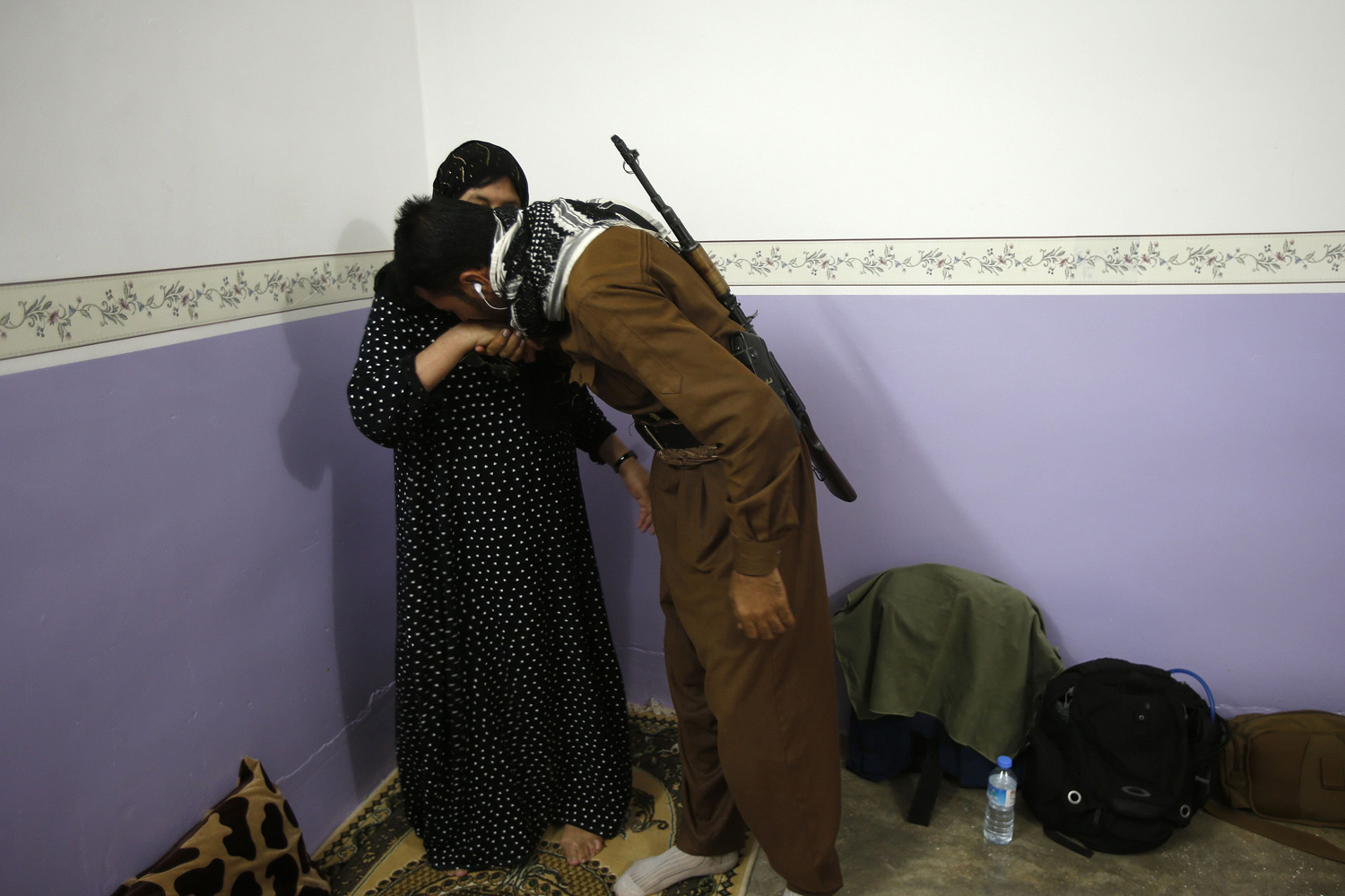 Aug. 31, 2014. A mother says goodbye to her son, a volunteer in the Kurdish peshmerga forces, as he prepares to leave home for the front line near Tuz Khurmatu, northeast of Tikrit city.