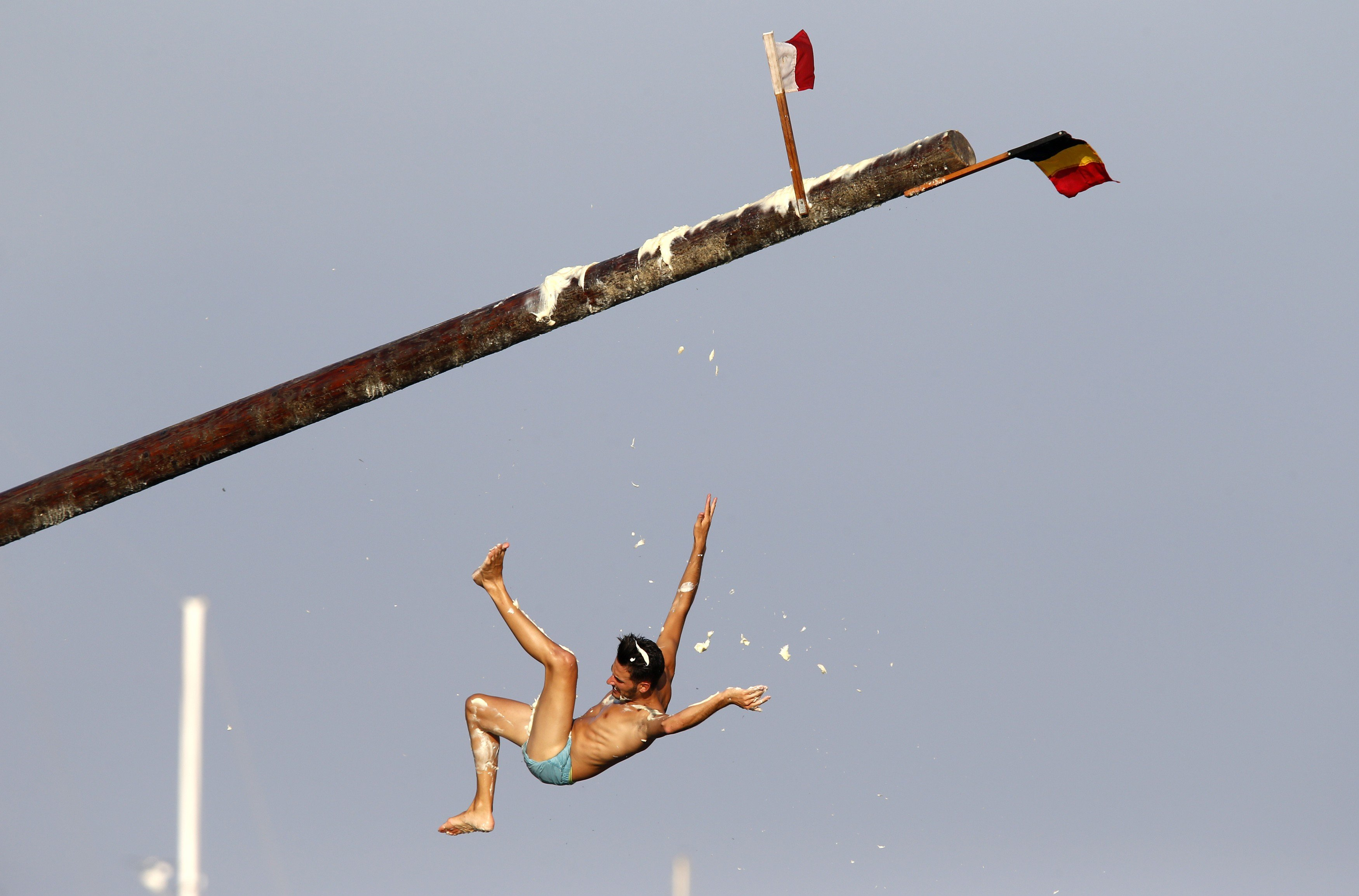 A man falls off the  gostra , a pole covered in grease, during the celebrations for the religious feast of St Julian, patron of the town of St Julian's, outside Valletta on Aug. 31, 2014.