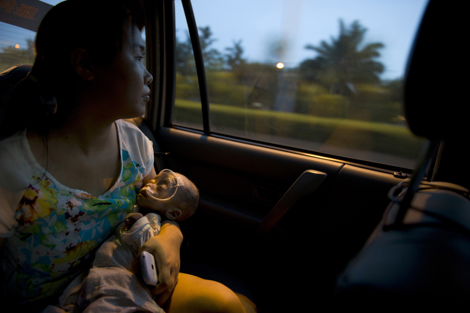 Aug. 30, 2014. Wu Lunjiao (L), holds her daughter Yuanyuan, who is suffering from an unknown disease, as she looks out of the window on a taxi in Shenzhen, Guangdong province.