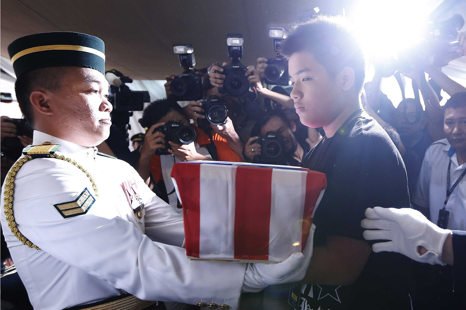 Sept. 2, 2014. Melvic Choo, 13, accepts the ashes of his father, MH17 co-pilot Eugene Choo, at his wake in Seremban. Malaysian Airlines (MAS) Flight MH17 crashed after being shot down over war-torn Ukraine on July 17, killing all 298 people on board.