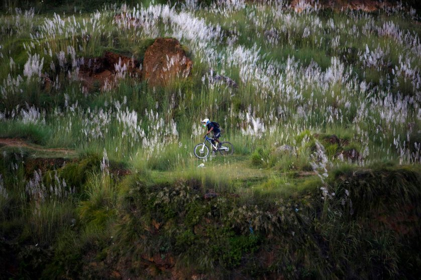 A youth rides a bicycle on the hills in Kathmandu