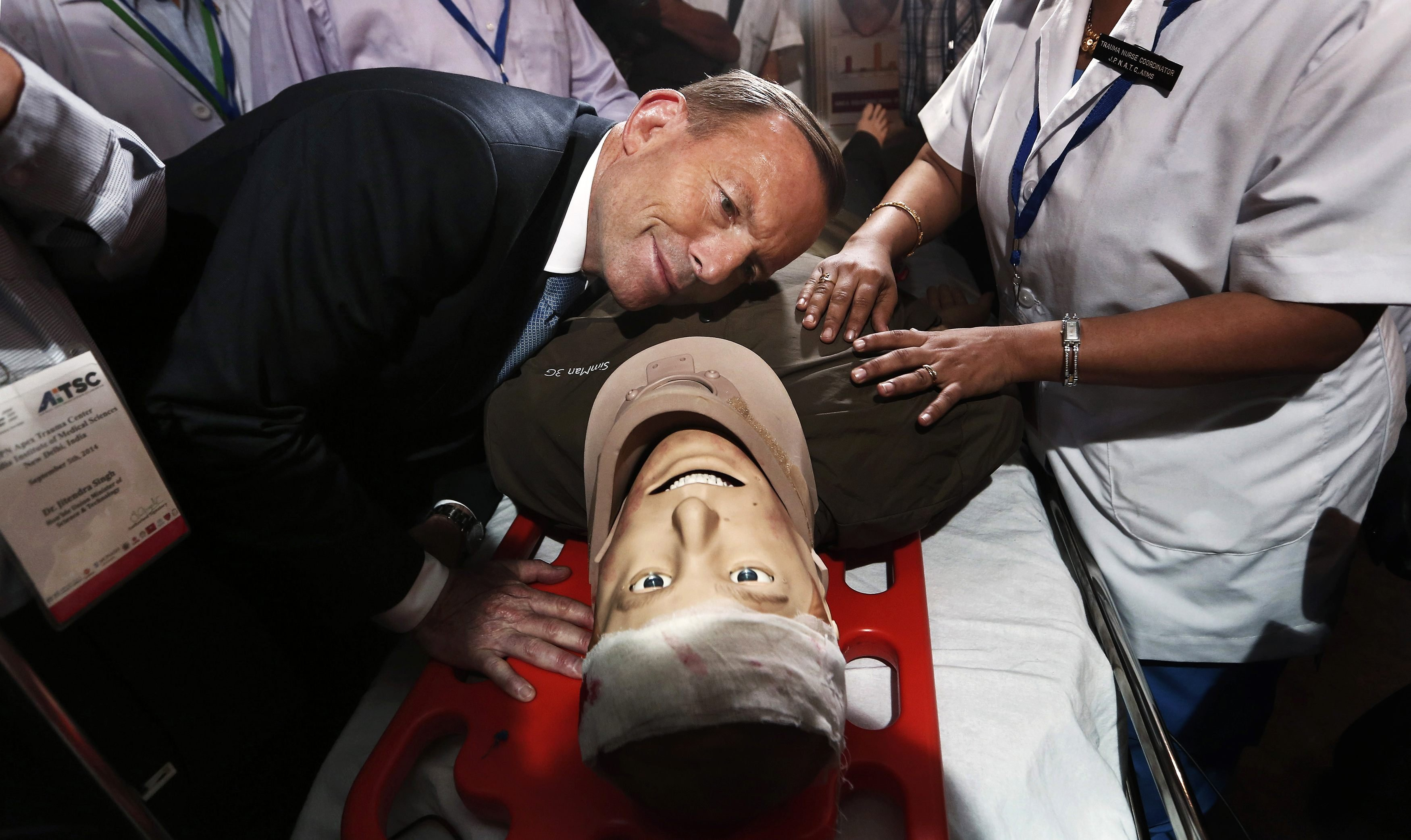 Australian Prime Minister Tony Abbott takes part in a presentation with a patient simulator during his visit to the trauma centre of the All India Institutes of Medical Sciences in New Delhi on Sept. 5, 2014.