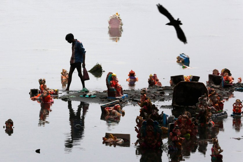 A boy collects items thrown by devotees as religious offerings next to idols of the Hindu elephant god Ganesh a day after they were immersed in the waters of the Sabarmati river in Ahmedabad