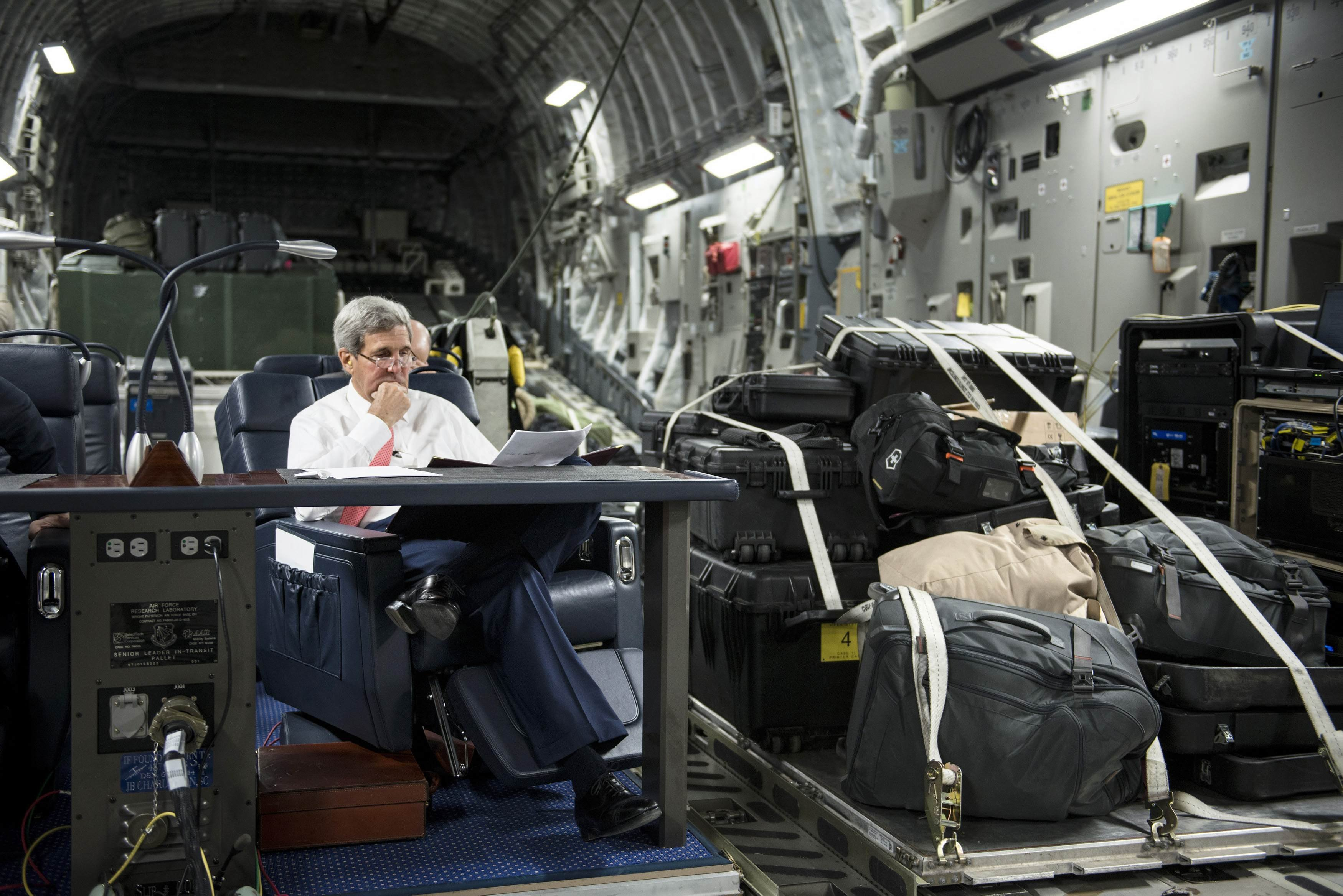 U.S. Secretary of State John Kerry looks over papers while flying from Jordan to Iraq on Sept. 10, 2014.