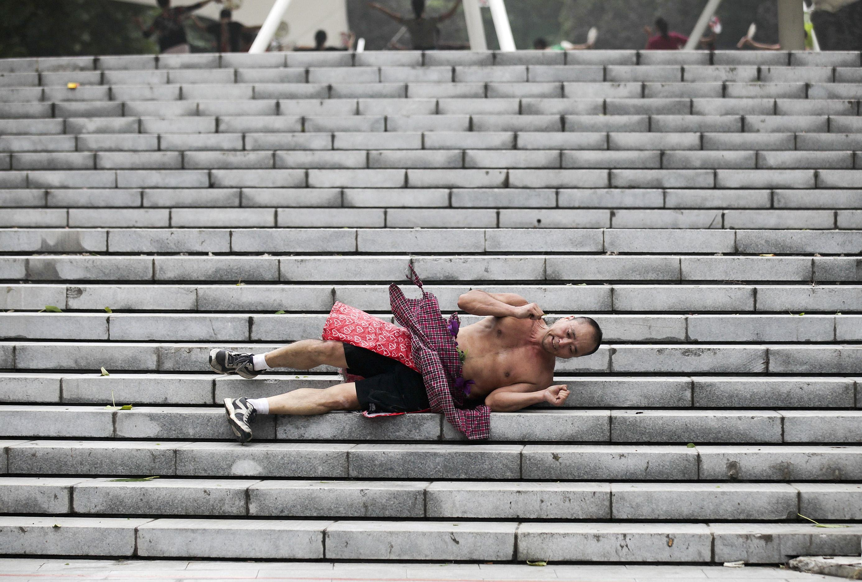 Li Zhiheng, an amateur athlete, holds up his hands as he rolls down a stairway during a morning exercise at a park in Xi'an, Shaanxi province on Sept. 11, 2014.