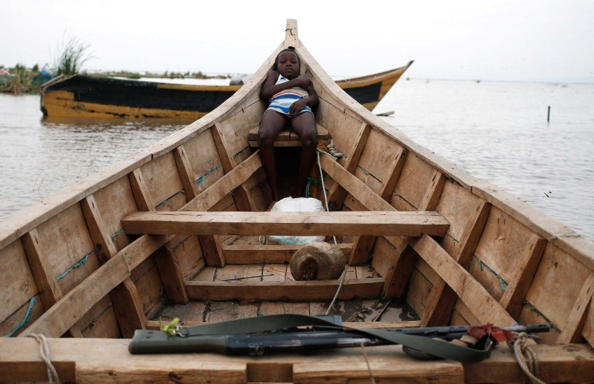 A Dassanach boy rests on a boat on the shore of a fishing camp near the Omo Delta in the north of Lake Turkana close to the town of Ileret and near the Kenyan-Ethiopian border in northern Kenya