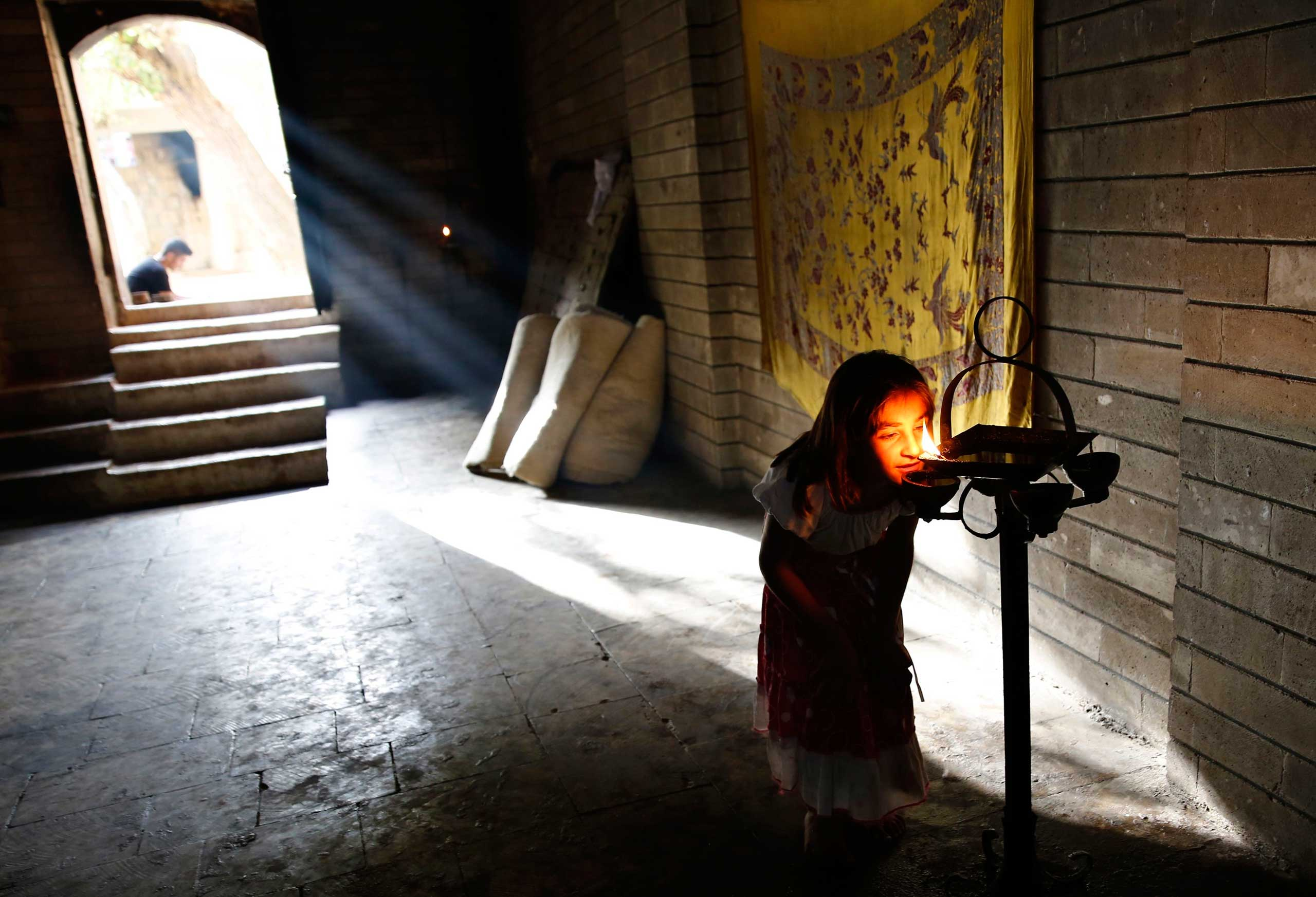Sept. 20, 2014. A displaced girl from the  minority Yazidi sect, who fled violence in the Iraqi town of Sinjar, worships at their main holy temple Lalish in Shikhan.