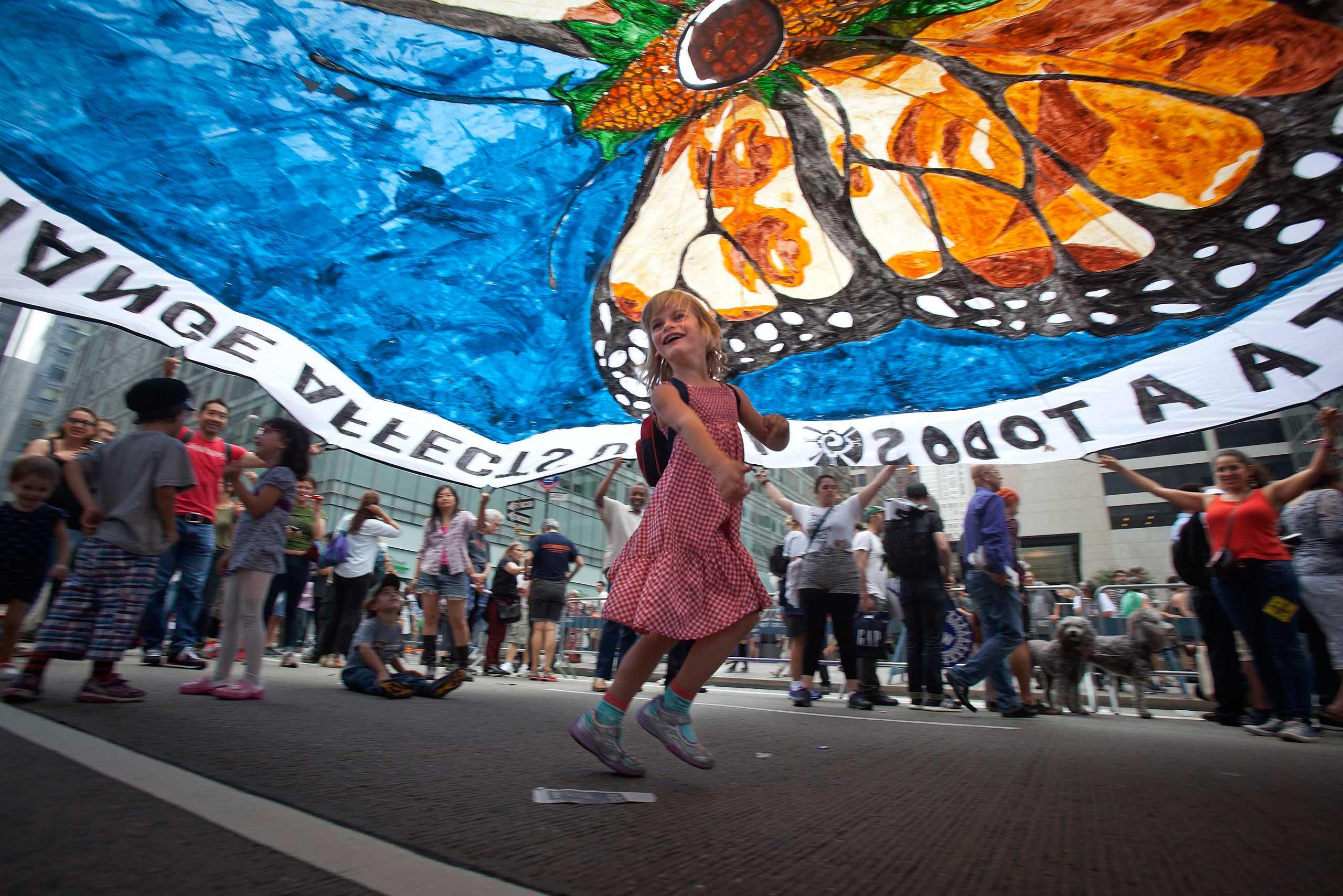 A girl dances under a protest parachute.