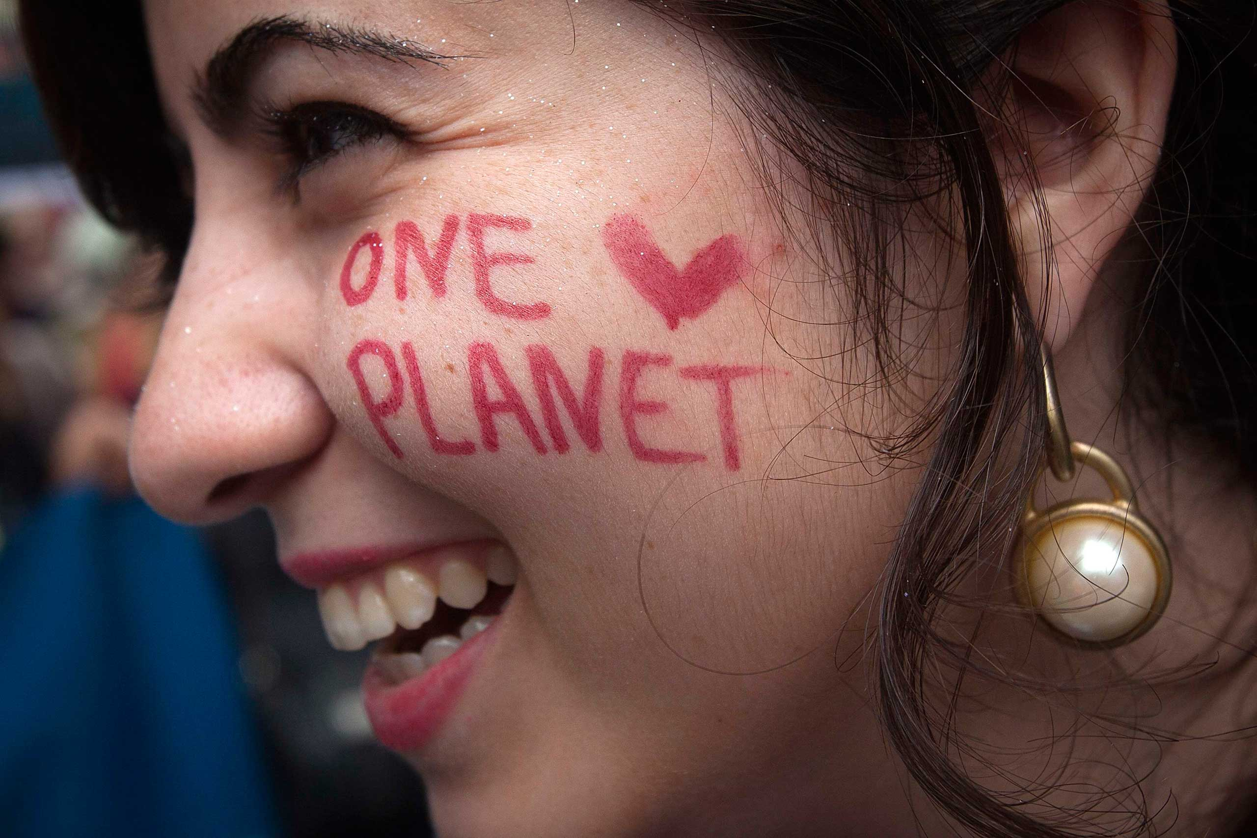 A protester with  One Planet  drawn on her face takes part in the  People's Climate March  down 6th Ave.