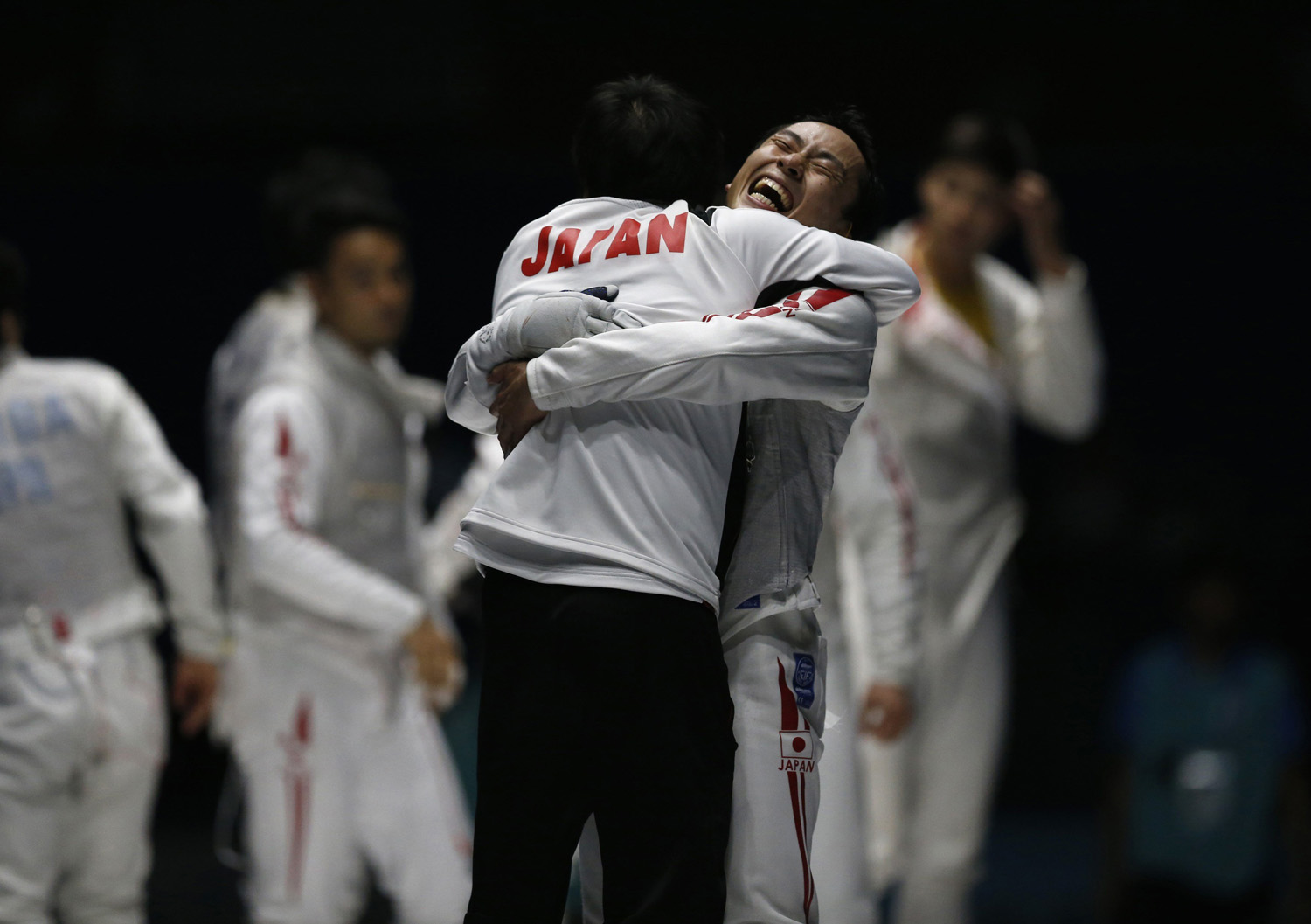 Japan's Yuki Ota (R) celebrates with a team member after winning their men's foil team fencing competition final against China at Goyang Gymnasium during the 17th Asian Games in Incheon, South Korea, on  Sept. 25, 2014.