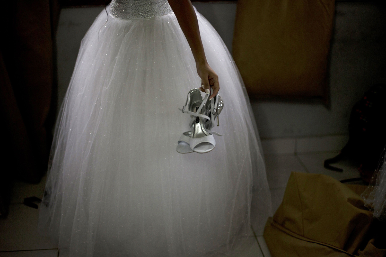 Aug. 29, 2014. A teenage girl from the Santa Marta  favela  slum holds a pair of high heels before the start of a debutante ball organized by the Pacifying Police Unit from her neighborhood in Rio de Janeiro, Brazil.