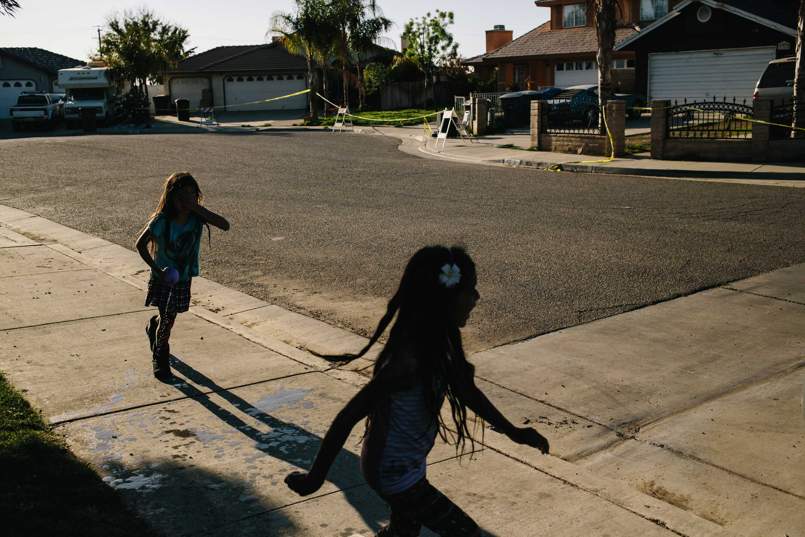 Samantha Olivarez, 9, left, and her cousin, Daisy Olivarez, 7, play in front of their home in Arvin, Calif. The homes across the street were evacuated after a gas pipe leaked underground. According to reports, the 40-year-old pipe was leaking for as long as two years before it was detected. Olivarez's family is worried about possible health risks in the area due to the pollution.