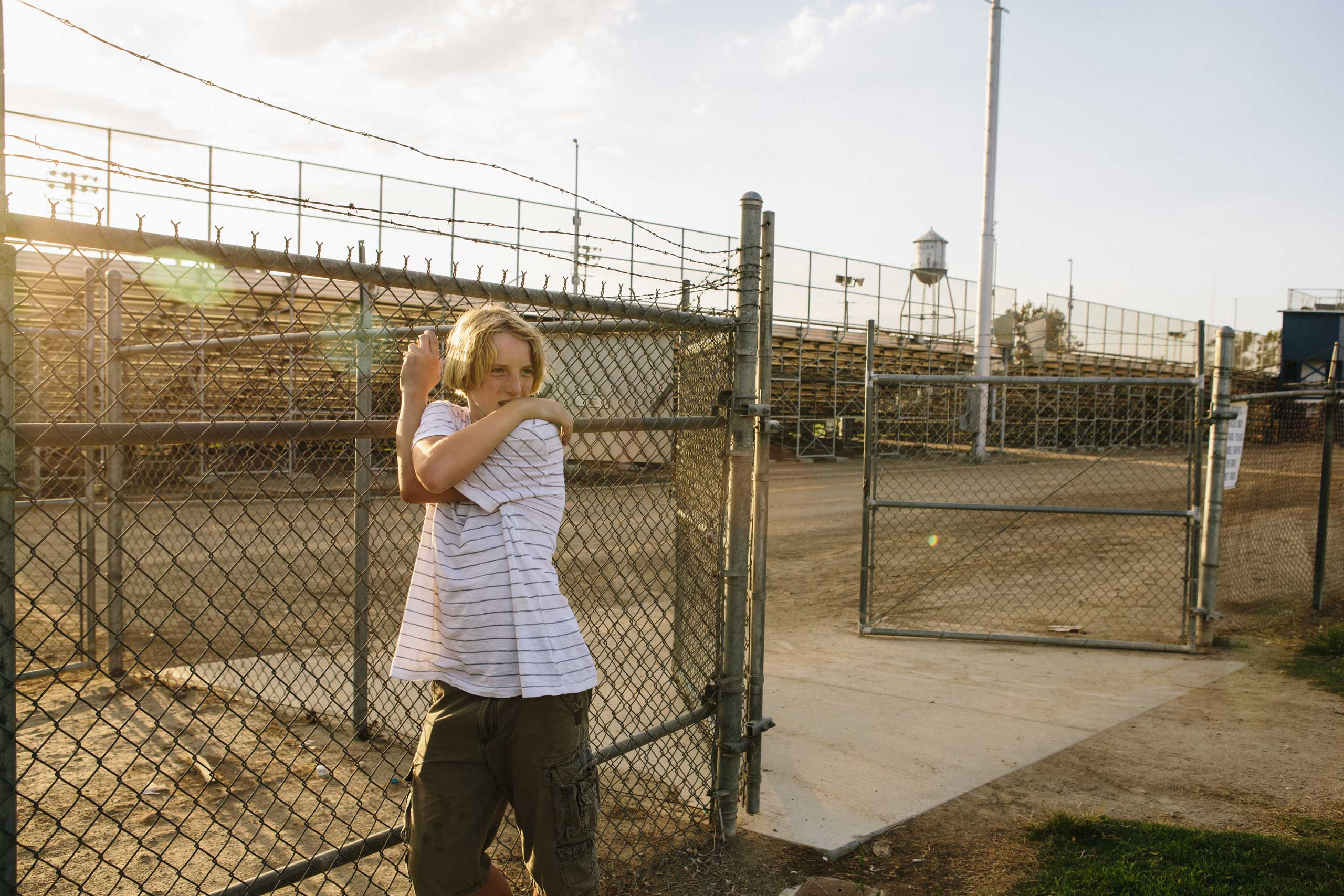 Benjamin Swall, 14, waits for his brother's football practice to end at Bakersfield High School.
