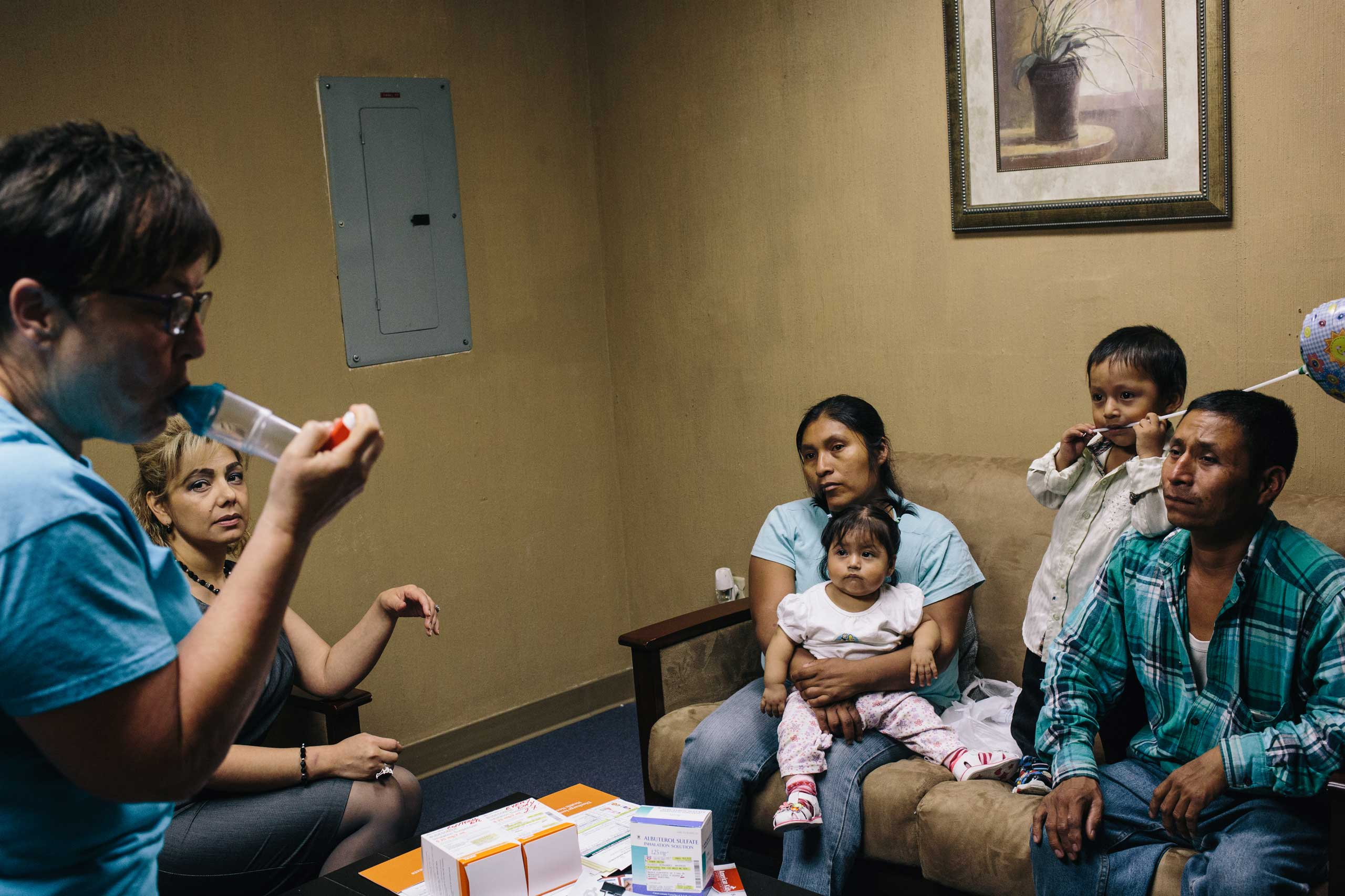 Asthma educator Sharon Borradori, left, shows Margarita Hernandez, center, and her husband, Severo Velasco, right, how their 2-year-old son, Mauricio Velasco will use an inhaler when he's older. Mauricio was recently released from the hospital after suffering from an extreme asthma attack.