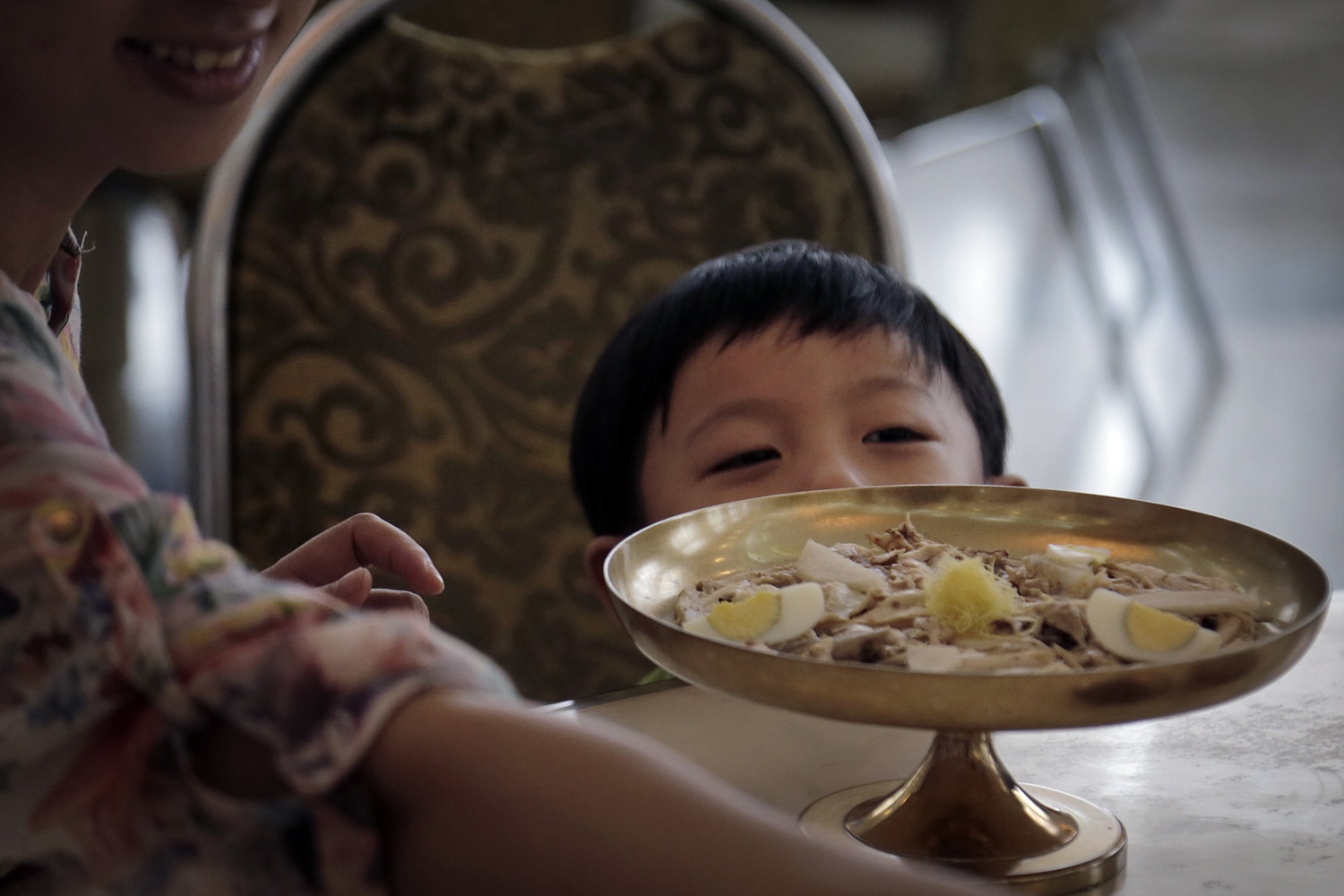 A young boy gazes toward his meal at the Ongnyugwan, a popular noodle restaurant in Pyongyang, Sept. 1, 2014.