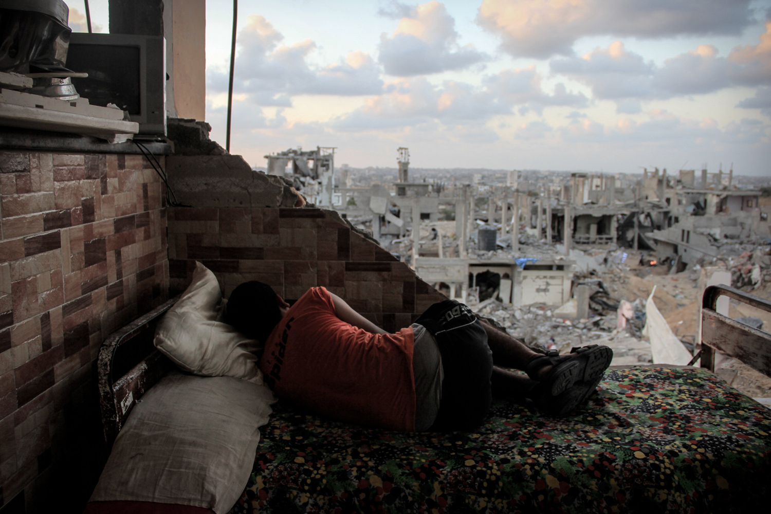 Sept. 1, 2014. A boy sleeps amid the rubble of his destroyed house in Gaza Strip.