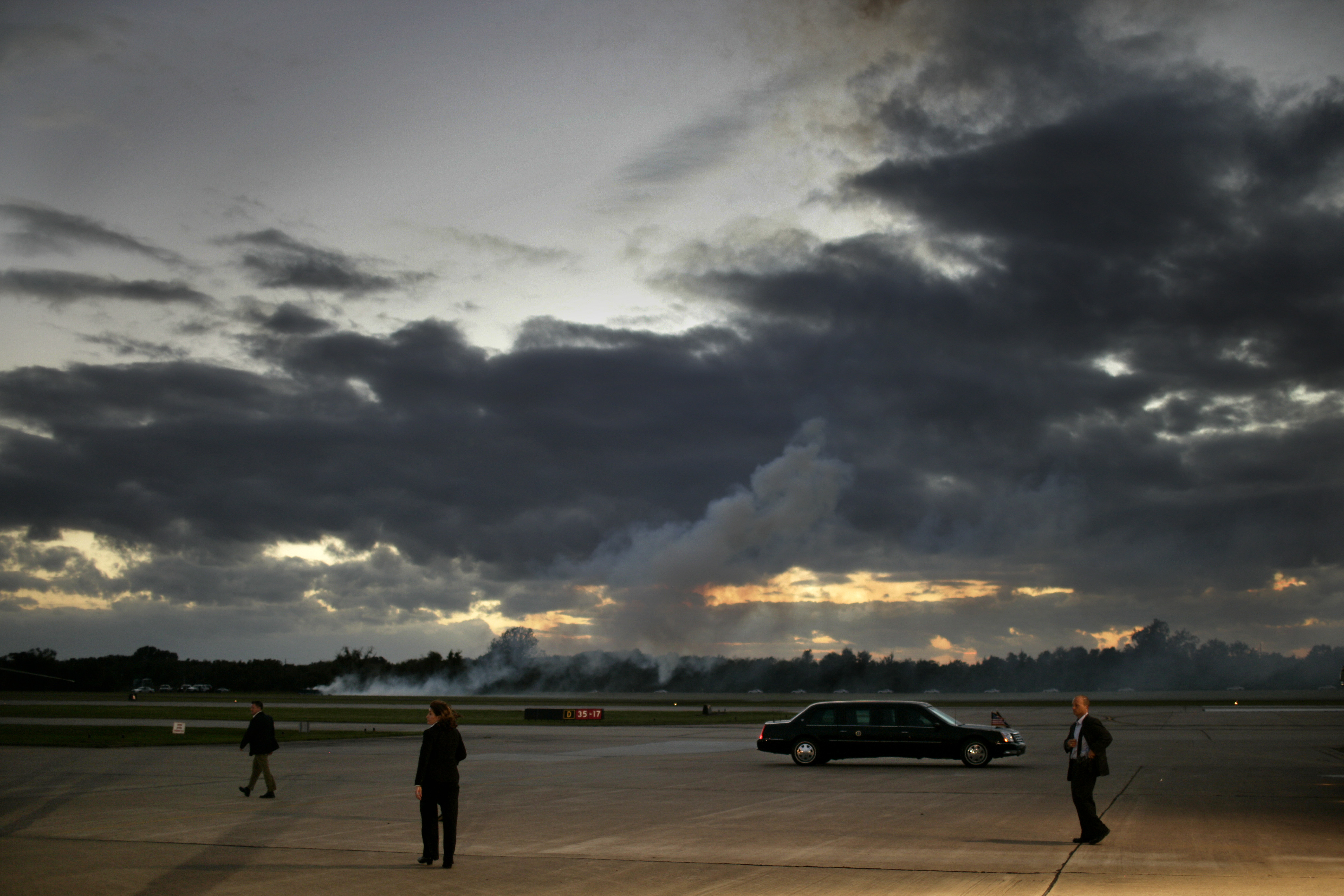 Secret Service agents stand near the Presidential Limousine at the conclusion of a campaign rally attended by President Bush in an airport hanger in Sugar Land, Texas on Oct. 30, 2006.