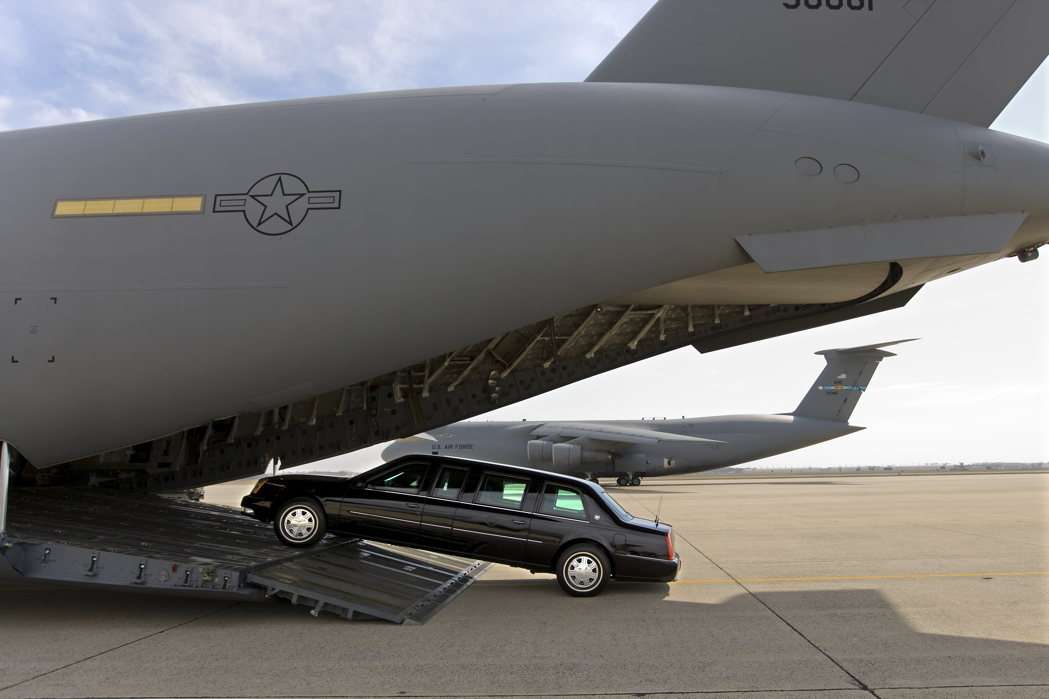 """A Presidential limousine is loaded onto a C5 military transport plane bound for eastern Europe, where President Bush is headed next week. A """"secure package"""" of motorcade vehicles, including the limousines and a fleet of Secret Service SUVs is transported to the site of every presidential visit, Maryland, March 28, 2008."""