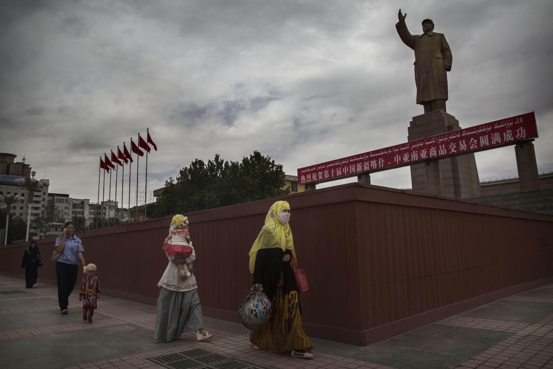 A veiled Muslim Uyghur woman walks passed a statue of Mao Zedong on July 31, 2014 in Kashgar, Xinjiang Uyghur Autonomous Region, China.