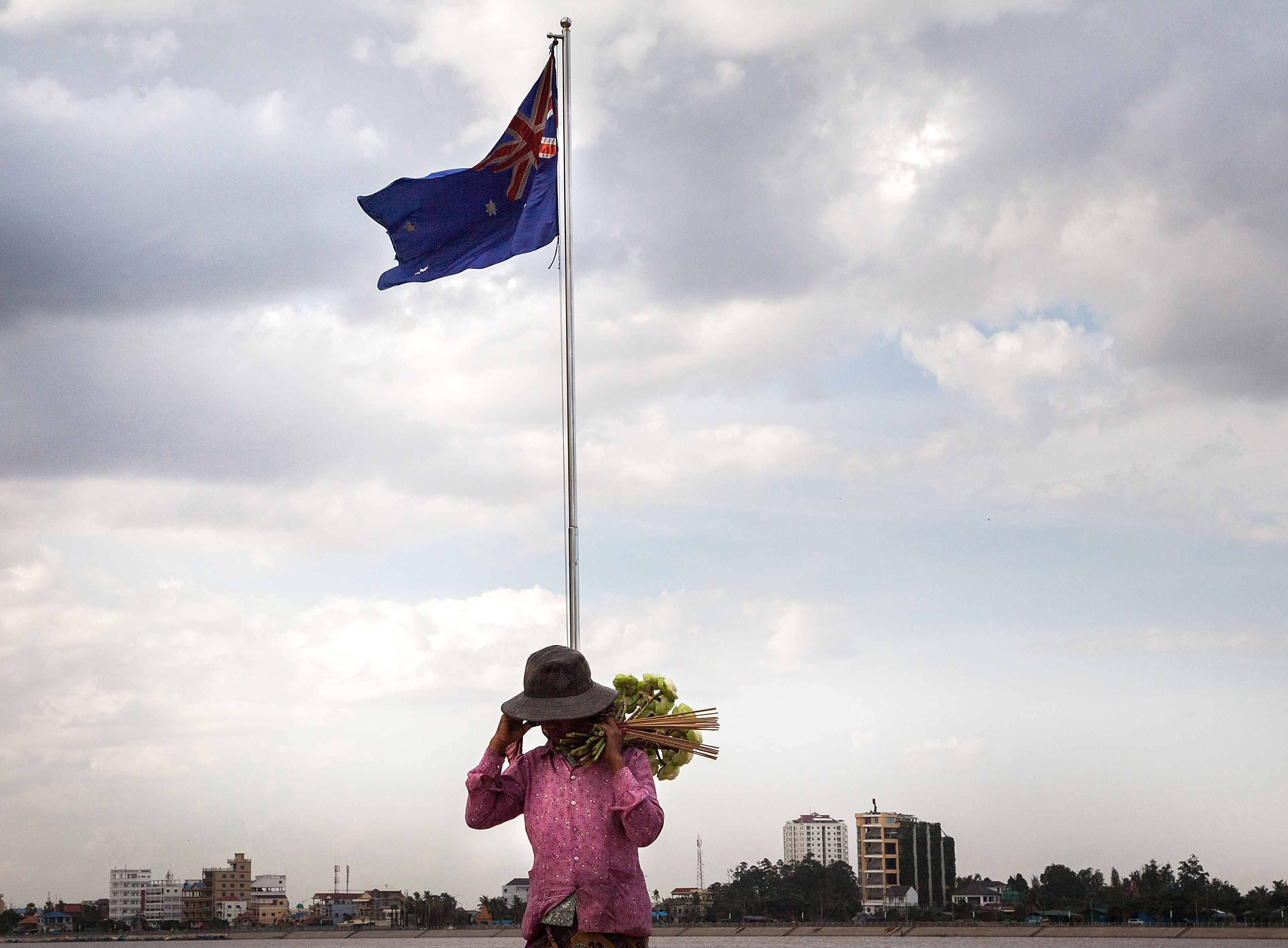 A lotus-flower seller stands underneath the Australian flag along the riverside in Phnom Penh on Aug. 13, 2014. After months of negotiations Australia and Cambodia look set to agree on a deal that will see 1,000 refugees transferred from Australia to Cambodia