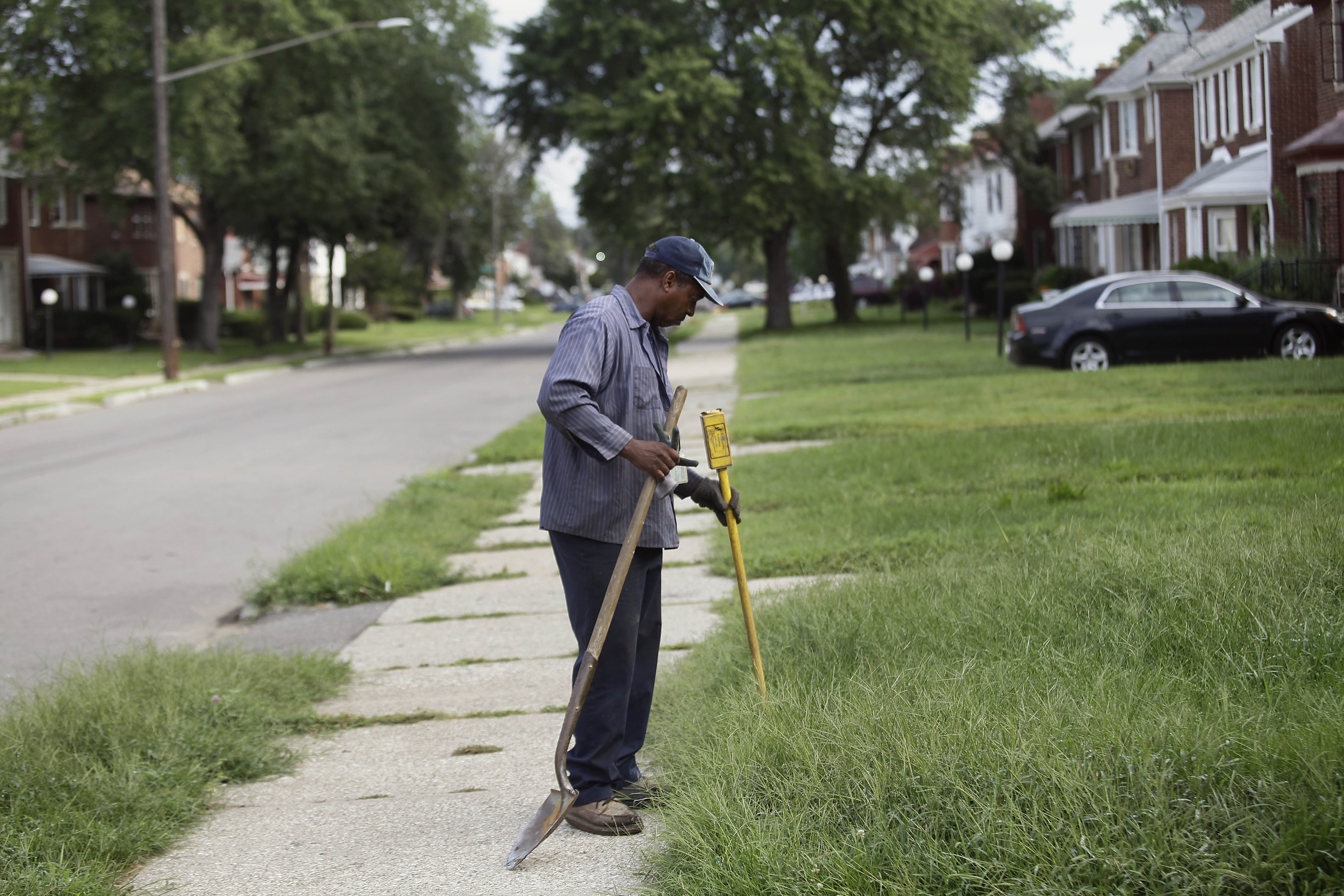 A worker from Homrich turns off water supply to a home August 27, 2014 in Detroit, Michigan. The Detroit Water and Sewer Department have disconnected water to thousands of Detroit residents who are delinquent with their bills.