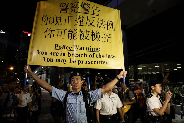 HONG KONG - AUGUST 31: A police officer holds a warning banner during a confrontation between Occupy Central protesters and police on August 31, 2014 in Hong Kong, China. The National People's Congress Standing Committee have endorsed a framework for political reform in Hong Kong ahead of the 2017 Chief Executive election, in which 3 candidates will be selected by a special committee, ruling out open nominations. Opposers to the plans, including pro-democracy group Occupy Central, argue that the system will not meet international standards and deprives people of a genuine choice of candidates. (Photo by Lam Yik Fei/Getty Images)