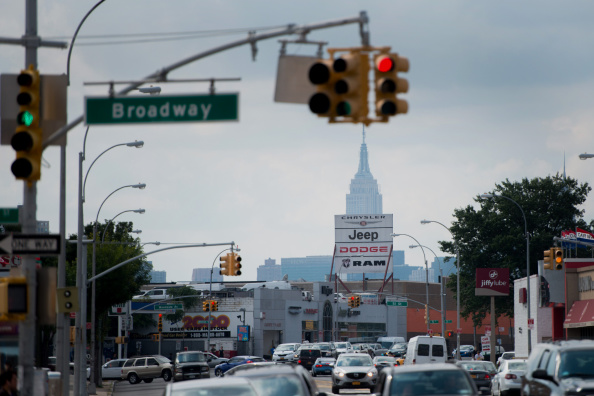 Vehicles drive past the Major Chrysler Jeep Dodge Ram dealership as the Empire State building stands in the background in the Queens borough of New York, U.S., on Monday, Sept. 1, 2014. Domestic and total vehicle sales figures are scheduled to be released on Sept. 3. Photographer: Craig Warga/Bloomberg via Getty Images
