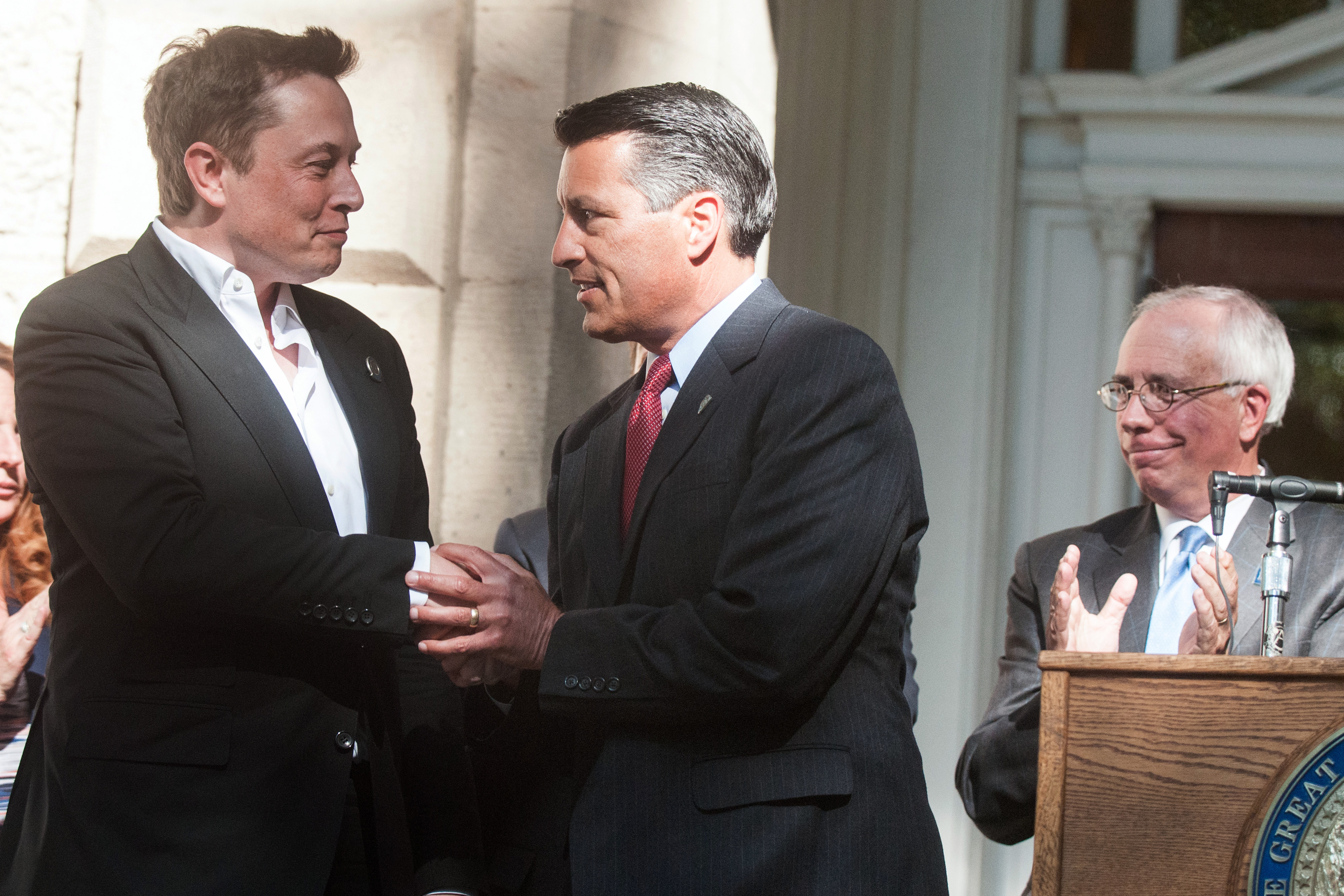 Brian Sandoval, Governor of Nevada, center, shakes hands with Elon Musk, co-founder and chief executive officer of Tesla Motors Inc., during a news conference at the Nevada State Capitol building in Carson City, Nevada, U.S., on Thursday, Sept. 4, 2014.