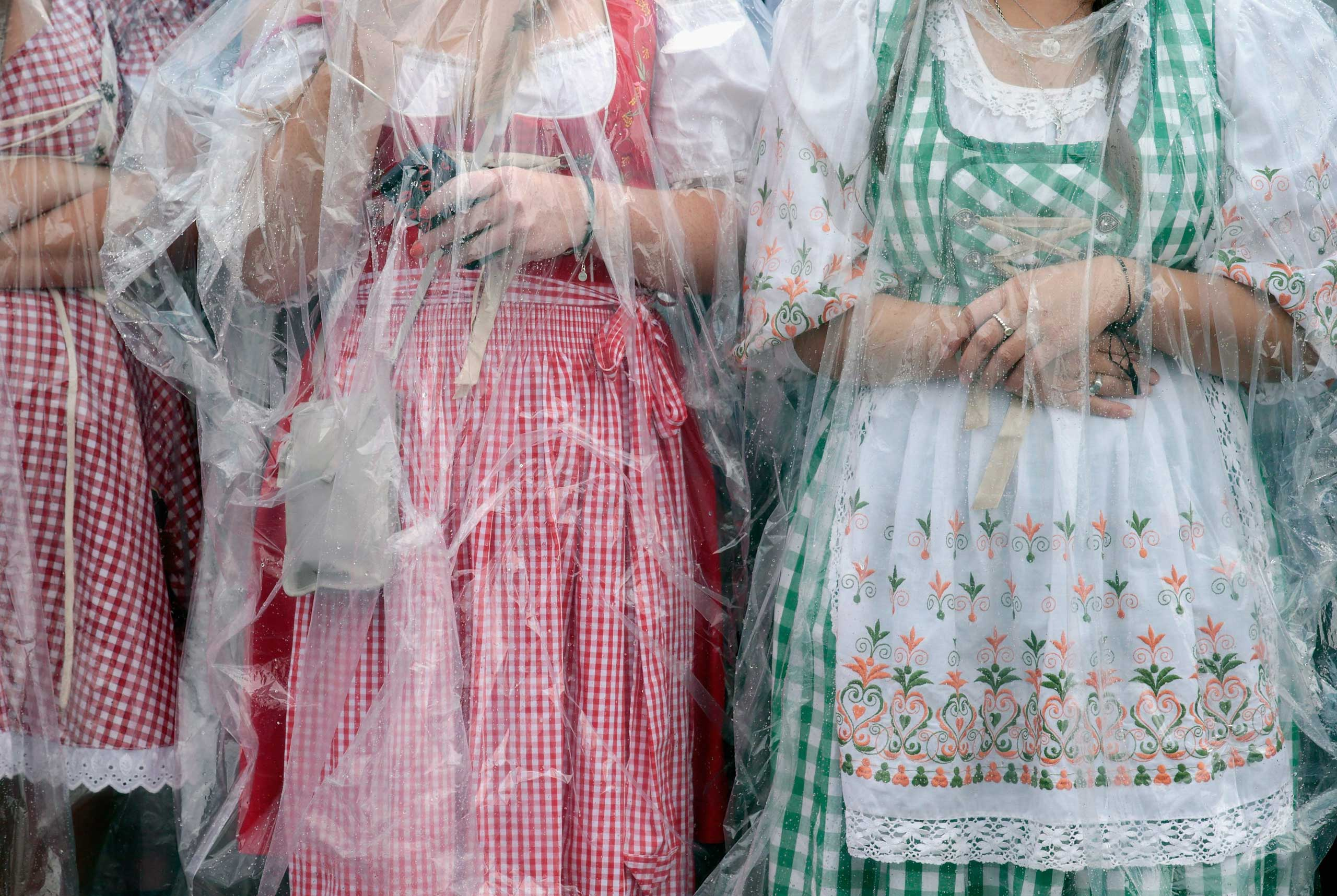 Sept 20, 2014. Revelers dressed in traditional Bavarian 'Dirndl' shelter themselves from the rain waiting for the opening parade during the first day of the 2014 Oktoberfest in Munch, Germany.