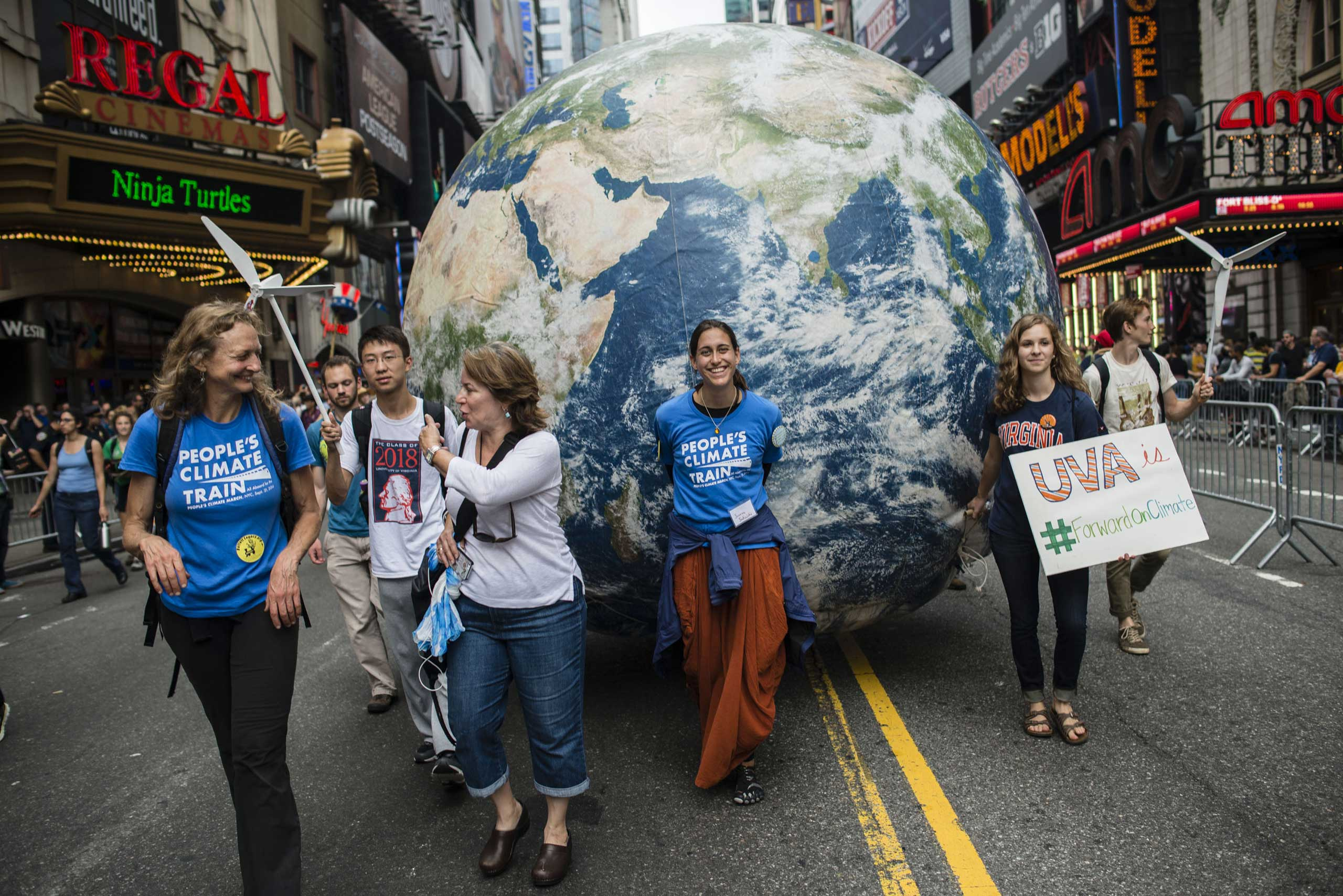 Marchers roll a model of planet Earth.