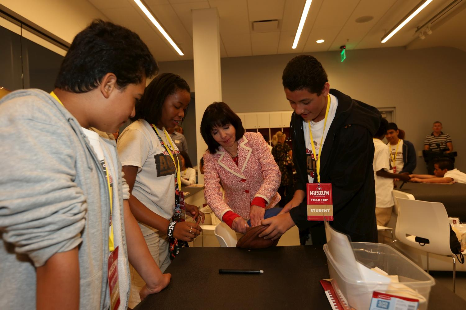 Denise DeBartolo York helps students assemble a football at the 49ers STEM Leadership Institute at Levi's Stadium