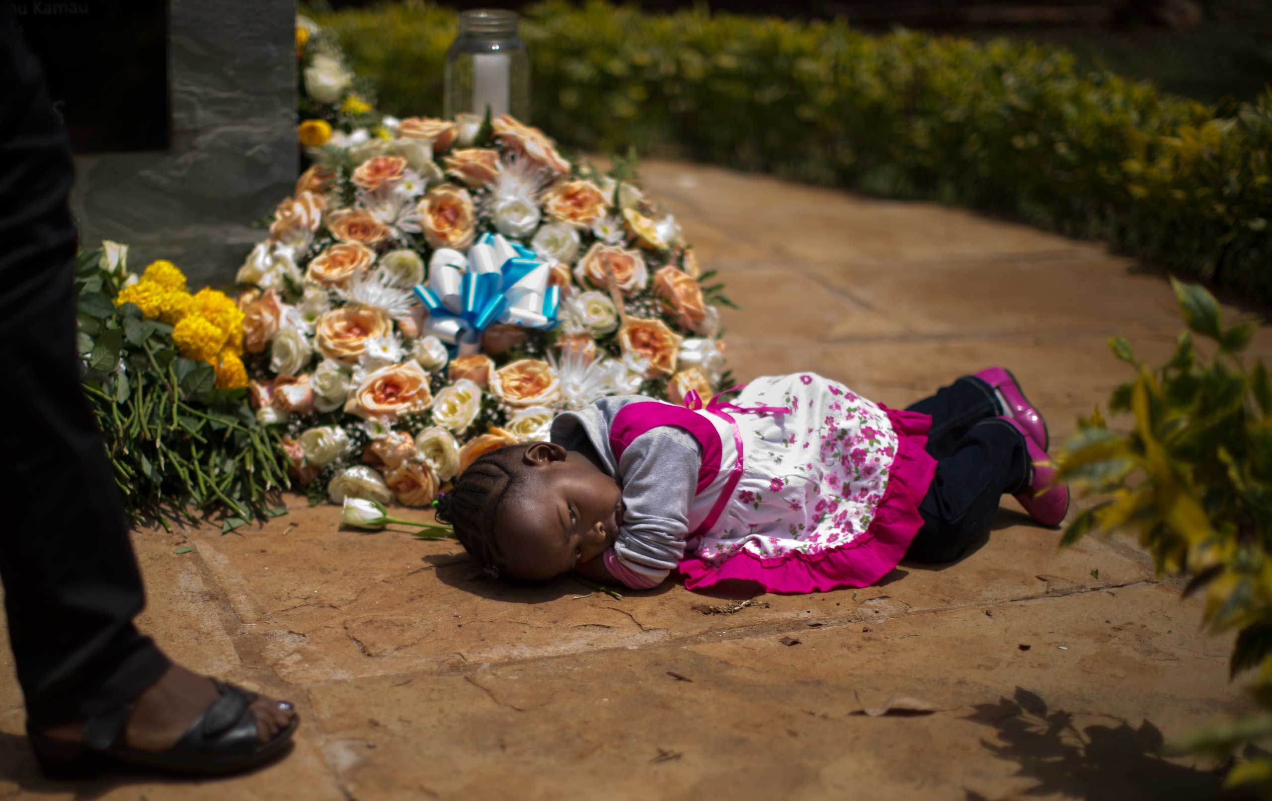 Sept. 21, 2014. Nicole Tashly, 2, lies quietly on the ground holding the white rose her mother Esther Muthoni, left, instructed her to lay at the memorial monument while they remember her father Paul Muriithi Muriuki who died in the Westgate Mall attack in Kenya.