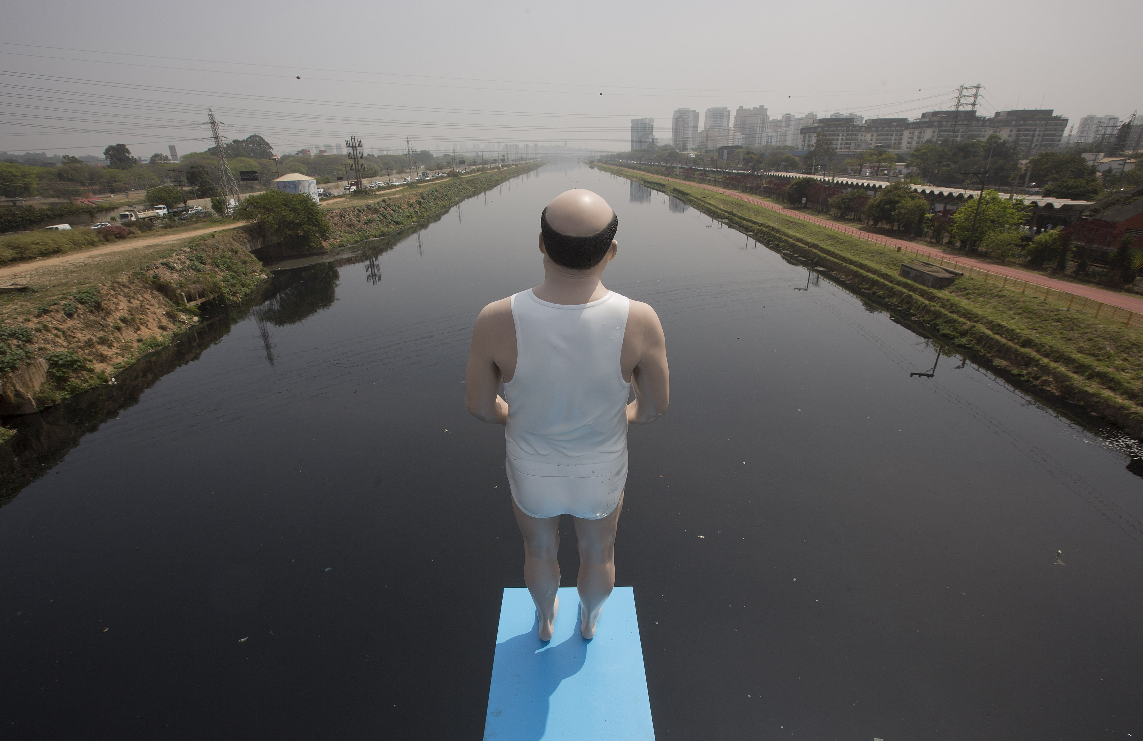 An art installation by Brazilian artist Eduardo Srur made with a life-size mannequin stands over the highly polluted Pinheiros River in Sao Paulo, Brazil on Sept. 18, 2014.