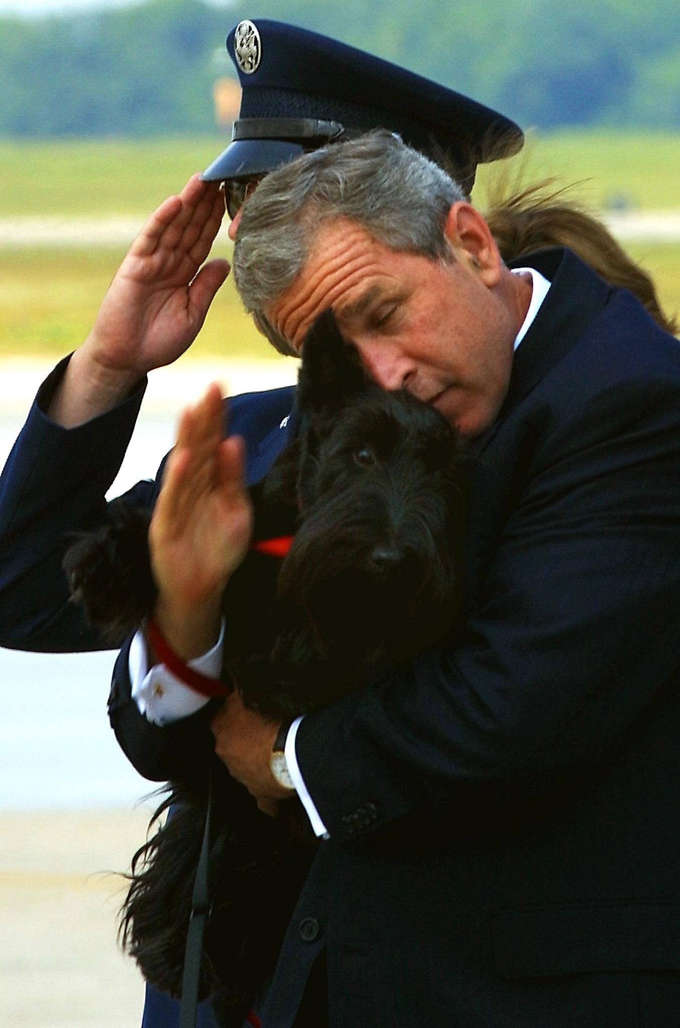 President George W. Bush tries to salute the security officers at the steps of Air Force One as he holds his dog Barney, after returning from a speech to the US Conference of Mayors in Detroit, MI.