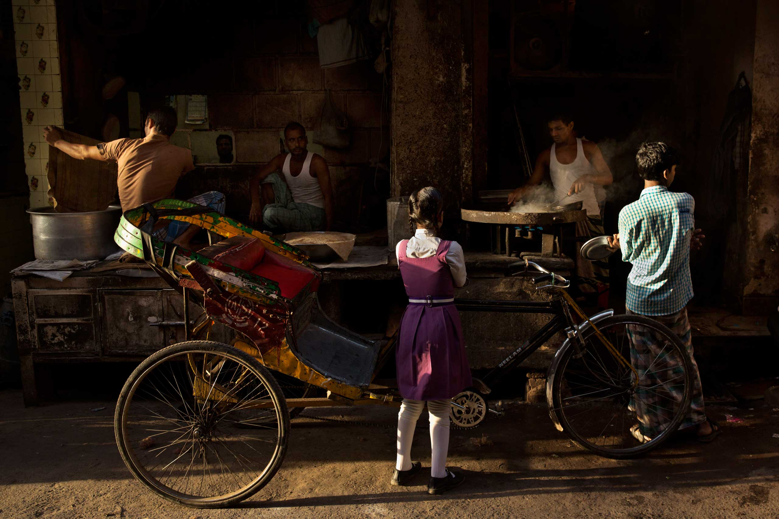 Sept. 22, 2014. An Indian schoolgirl and a boy wait to get breakfast in the old city area of New Delhi, India.