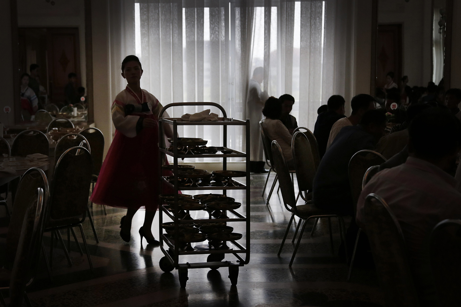 Sept. 1, 2014. A North Korean waitress is silhouetted as she pushes a trolley of noodles at the Ongyugwan dining hall of a popular noodle restaurant in Pyongyang, North Korea. The restaurant, built in 1960 at the instructions of the late leader Kim Il Sung, claims to serve 10,000 lunches a day.