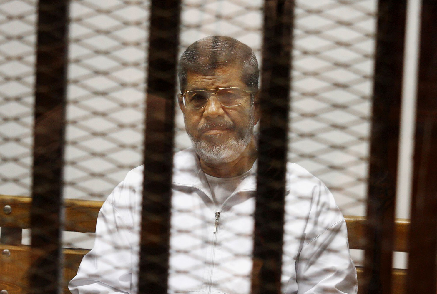 Egypt's ousted Islamist President Mohammed Morsi sits in a defendant cage in the Police Academy courthouse in Cairo, May 8, 2014.