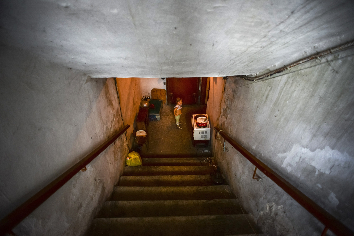Sept. 1, 2014. A little girl walks the stairs of the bomb shelter in Petrovskiy district in Donetsk, eastern Ukraine. Petrovskiy district of Donetsk is currently a frontline and one of the districts which suffered the most from the artillery fights between Ukrainian army and Pro-Pussian rebels.