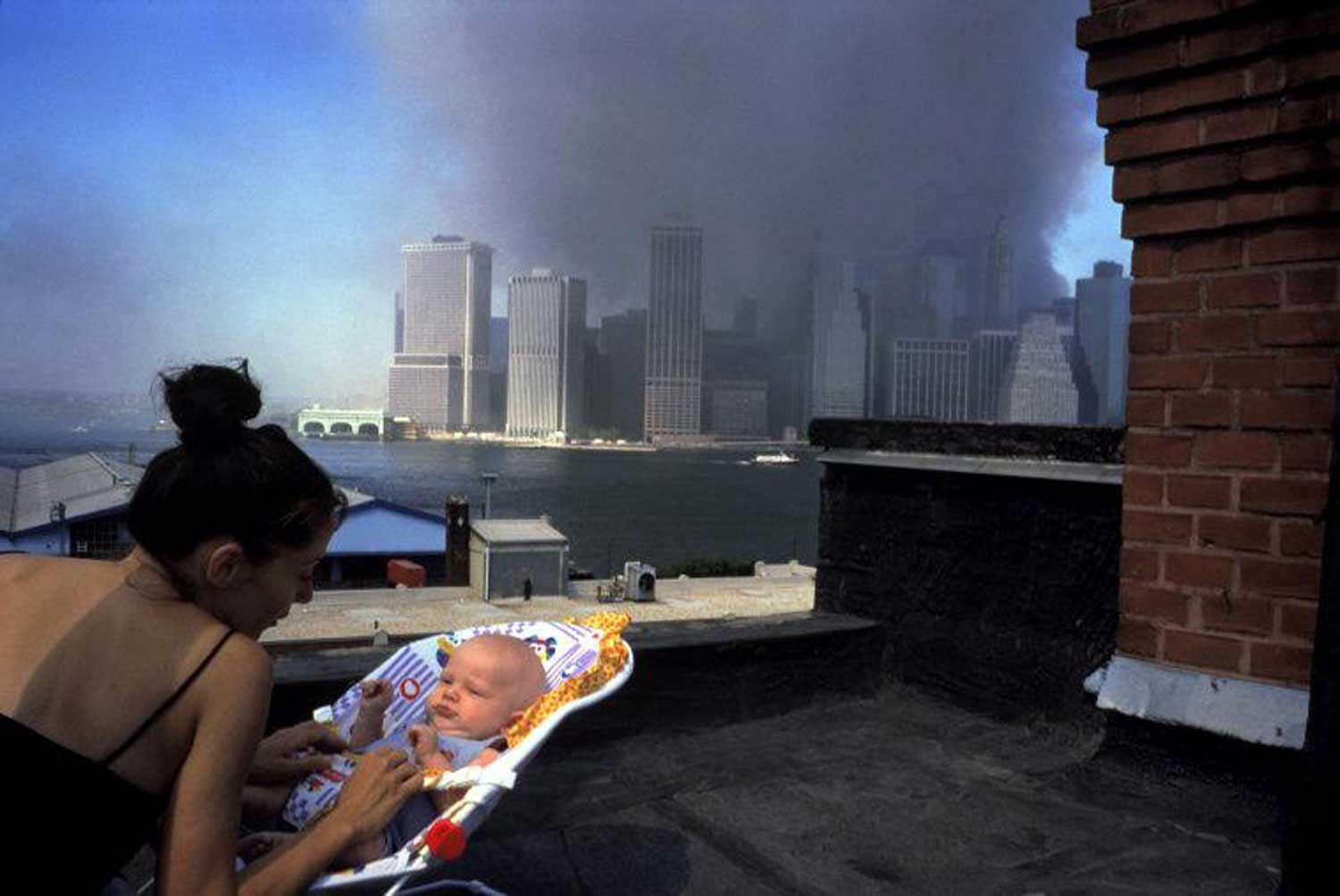 Alex Webb, photographer                                                               My wife Rebecca's and my first glimpse of lower Manhattan on September 11, 2001 was from a rooftop in Brooklyn Heights. That's where I took––probably on my first roll of film that day—what I consider my one singular image from Sept. 11—a mother and child with the smoldering ruins of the Twin Towers behind. It's a picture, in retrospect, that seems to me to suggest something about how life goes on in the midst of tragedy. Perhaps it also raises questions about what kind of future world awaits the child—and all of us. One reason this photograph continues to resonate with me is that the situation was different from violence that I'd witnessed in the past in places such as Haiti or Beirut. On September 11, 2001, not only was I photographing this particular mother and child in the city in which I lived, I was also aware of—out of the corner of my eye—another woman, my wife, the poet and photographer Rebecca Norris Webb. About an hour earlier and a few miles away in our apartment in Park Slope, Brooklyn, we were holding each other as we watched the second plane hit the second tower on our small TV. When I started to rush out the door with my cameras to head towards Manhattan, Rebecca—a photographer who has had little experience photographing conflict or violence—said she wanted to go with me. I balked. Shouldn't she stay in Brooklyn, away from the chaos of lower Manhattan? Perhaps I shouldn't even go—a startling notion for a photographer like myself who has covered situations of conflict in the past? And what might happen next to our city on that terrible morning? What if we were separated and unable to communicate during another wave of violence? Amid the chaos and the uncertainty, we chose to stay together and do one of the few things we know how to do—respond with a camera. Looking back ten years later, I'm not sure I would have seen this particular photograph—with its note of tendern