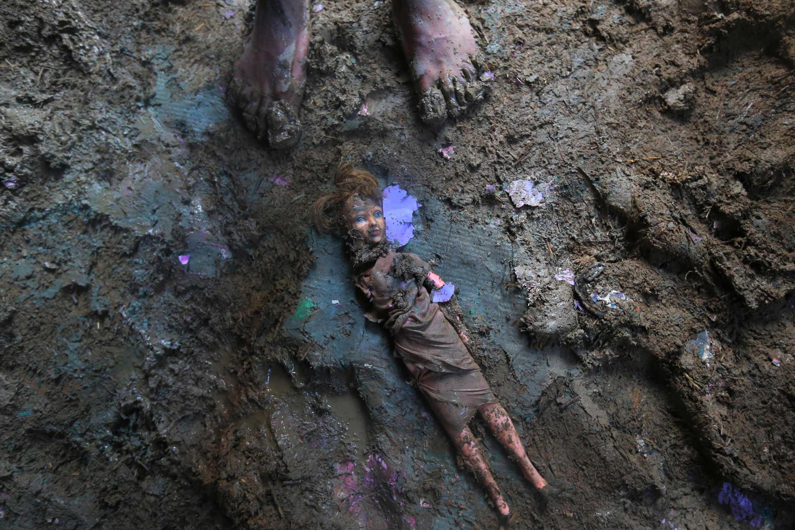 Sept. 19, 2014. A Kashmiri stands near a doll smeared with mud inside a flood damaged house in Srinagar,  India.