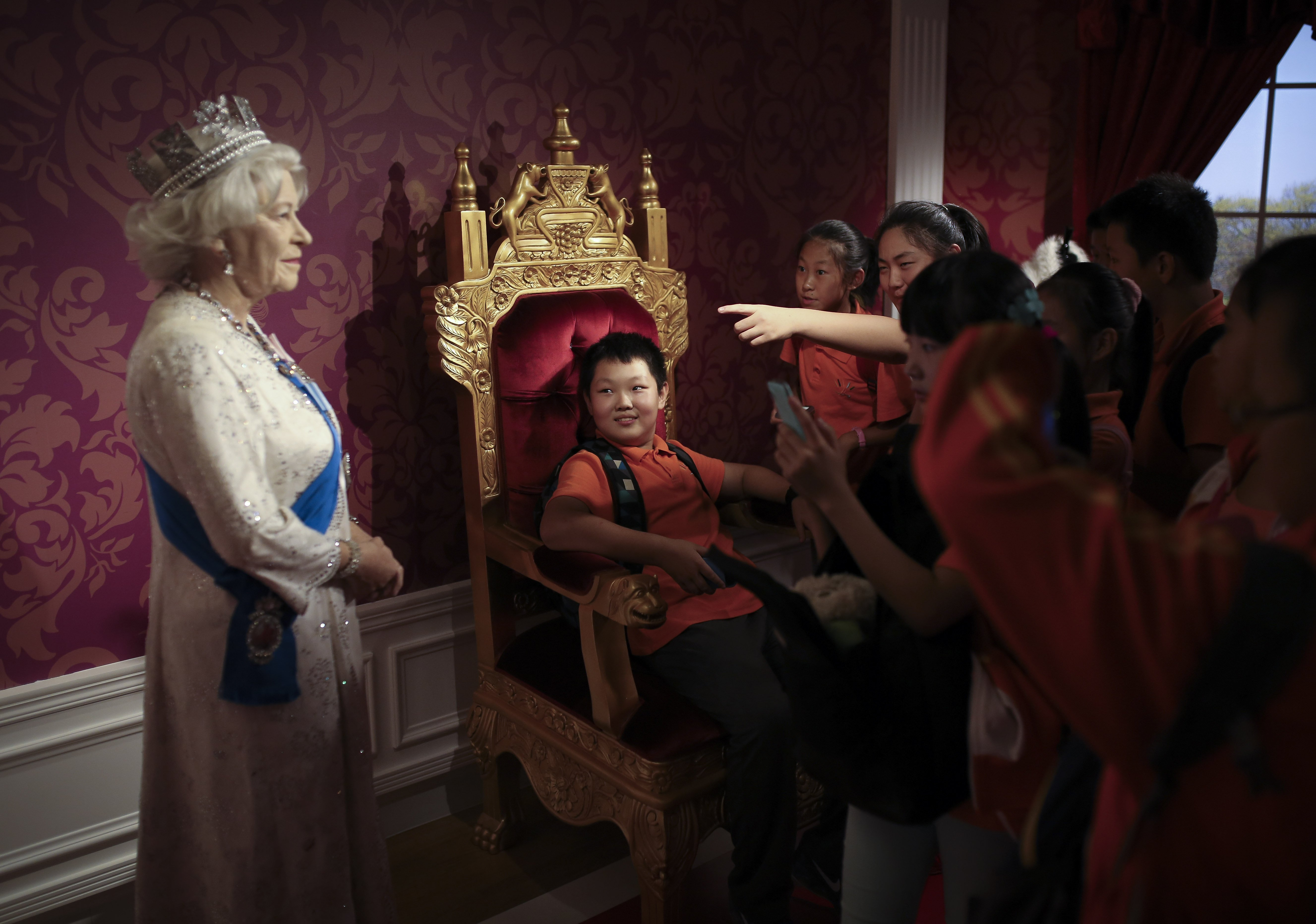 A student sitting on a mock-up of the royalty chair, looks at a wax figure of Britain's Queen Elizabeth II, while others take souvenir photos, at the Madame Tussauds Museum in Beijing on Sept. 19, 2014.