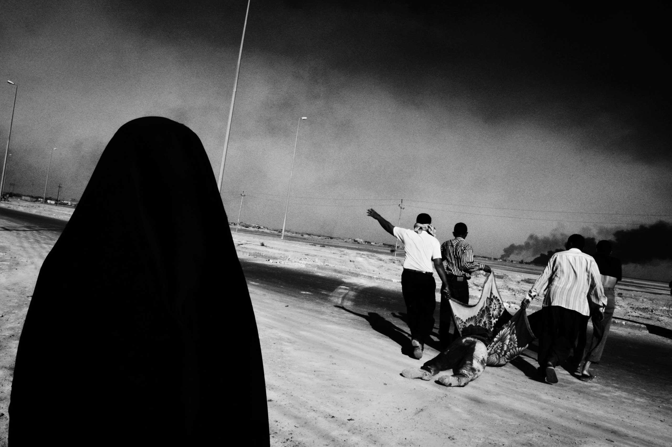 <b>Paolo Pellegrin, March 4, 2003                                   </b>                                   I entered Iraq unembedded with a car I had rented in Kuwait, stopping to photograph the fighting in Basra, a city in the South on the highway to Baghdad. The picture was taken near some sort of compound where there had been fighting between pro-Saddam fighters and British forces. There were several bodies of Iraqi fighters lying around. At one point, people started to appear on the streets to drag away particular bodies. As I understand, the woman in the foreground of the photograph was the mother of the deceased. They dragged him from the place he was killed, put him in the trunk of a waiting car, and drove off.                                    When I look at this image ten years later, the first thing that comes to mind is the idea of loss. I see the photograph and think of the mother's loss. If I continue looking, that black veiled figure, in some strange sense, makes me think of death itself - shadowy and dark.